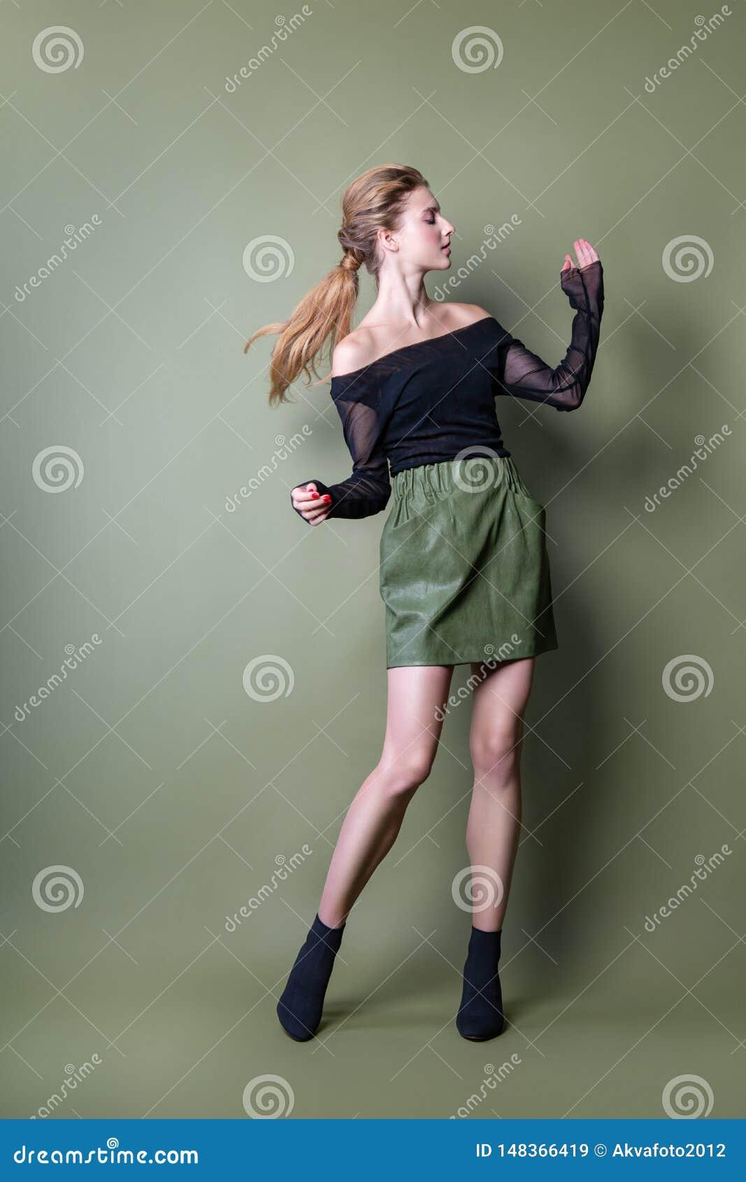 摆在演播室的一条黑夹克和绿色裙子的年轻美女 在时髦的便服的有吸引力的女性模型
