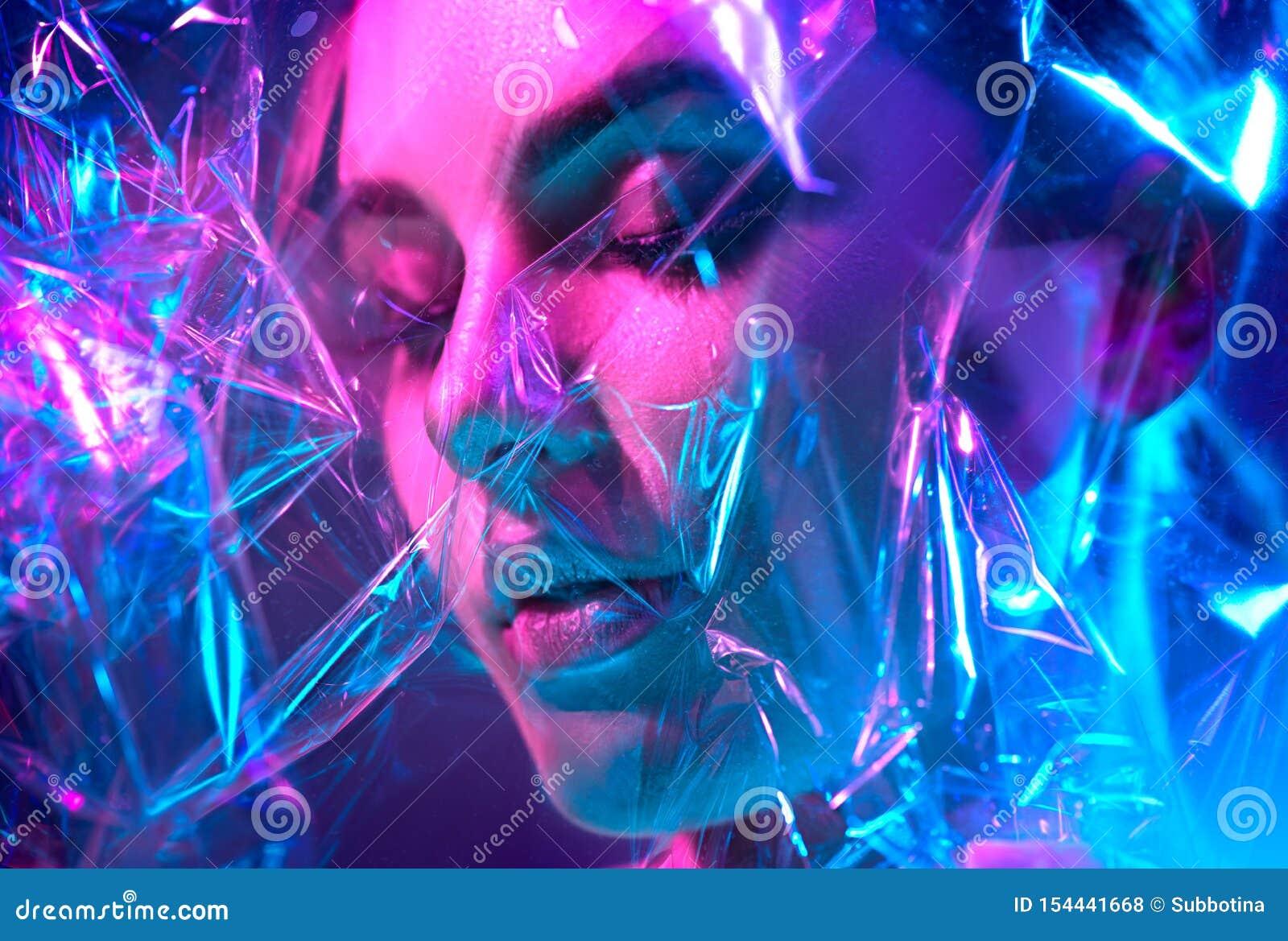 摆在演播室的五颜六色的明亮的霓虹灯的时装模特儿妇女通过透明影片 美女画象紫外的
