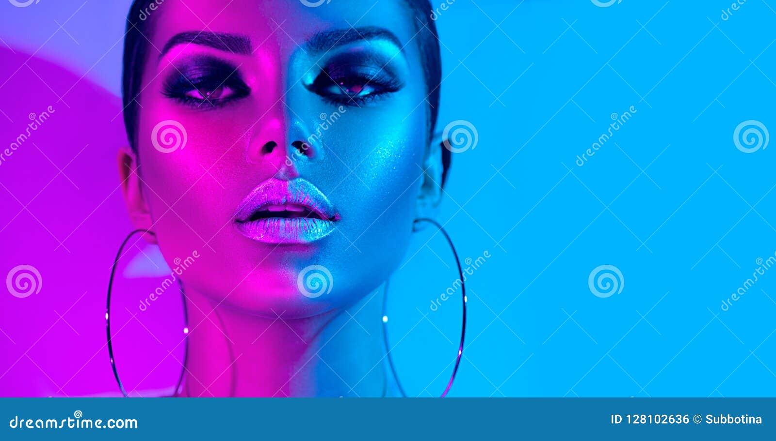 摆在演播室的五颜六色的明亮的霓虹灯的时装模特儿深色的妇女 美丽的性感的女孩,时髦发光的构成