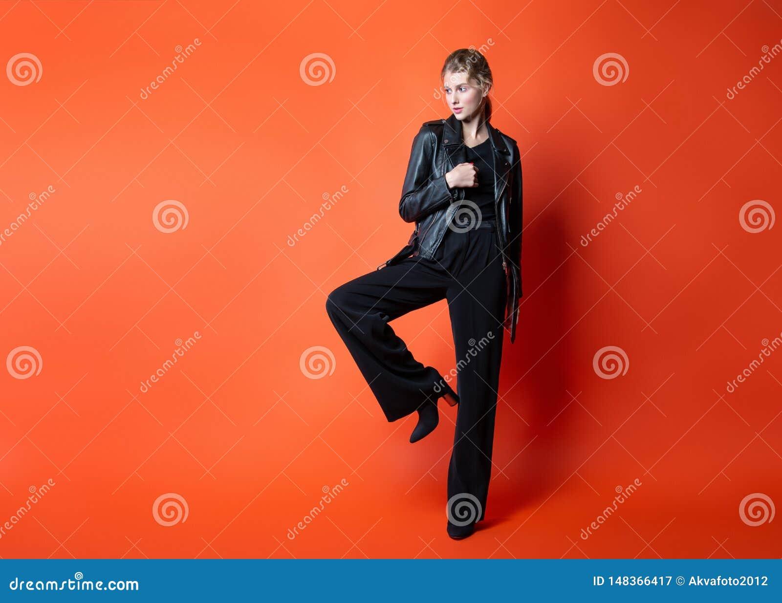 摆在演播室的黑色衣服的年轻美女 在时髦的便服的有吸引力的女性模型