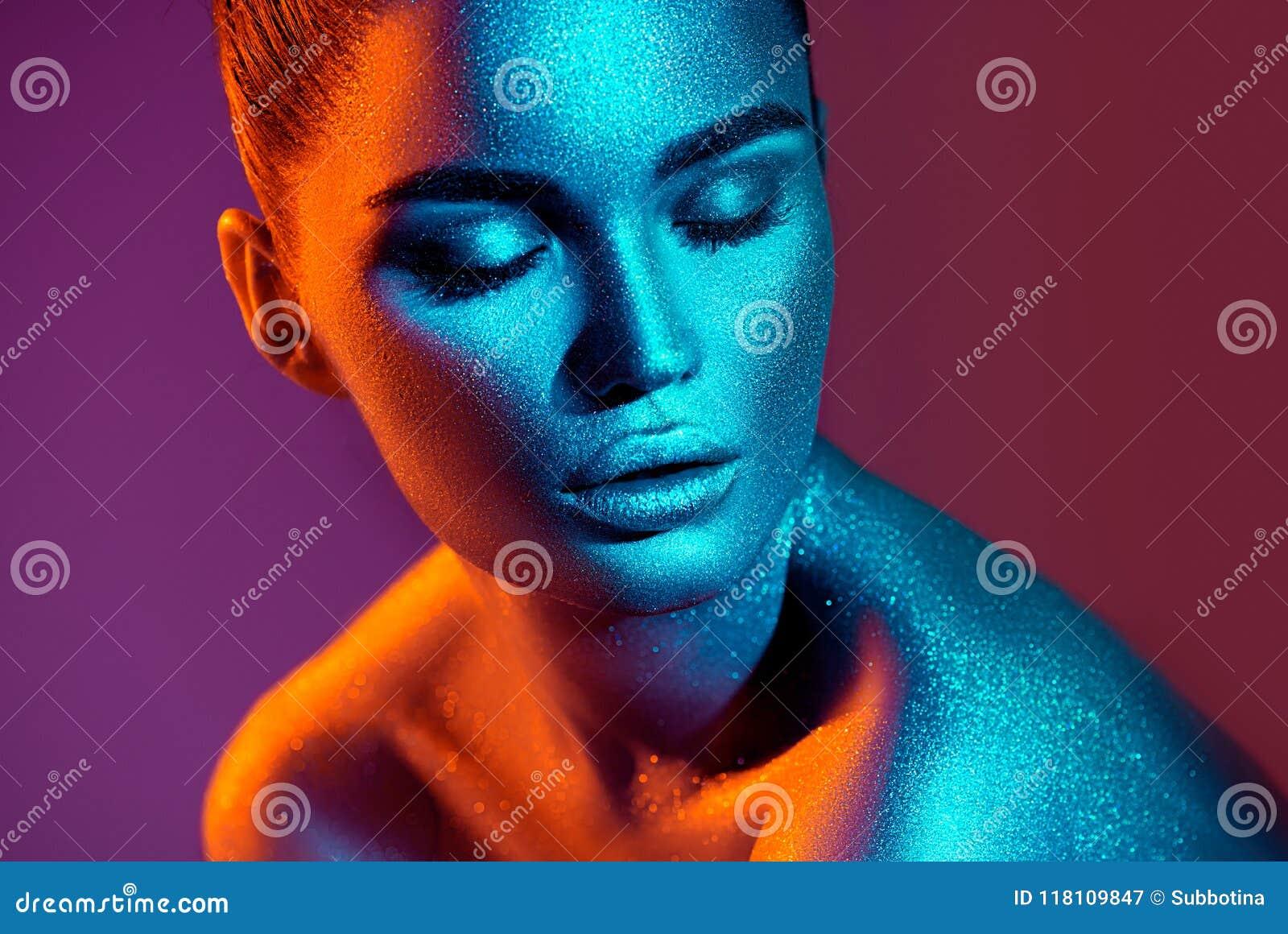 摆在演播室,美丽的性感的女孩画象的五颜六色的明亮的闪闪发光和霓虹灯的时装模特儿妇女