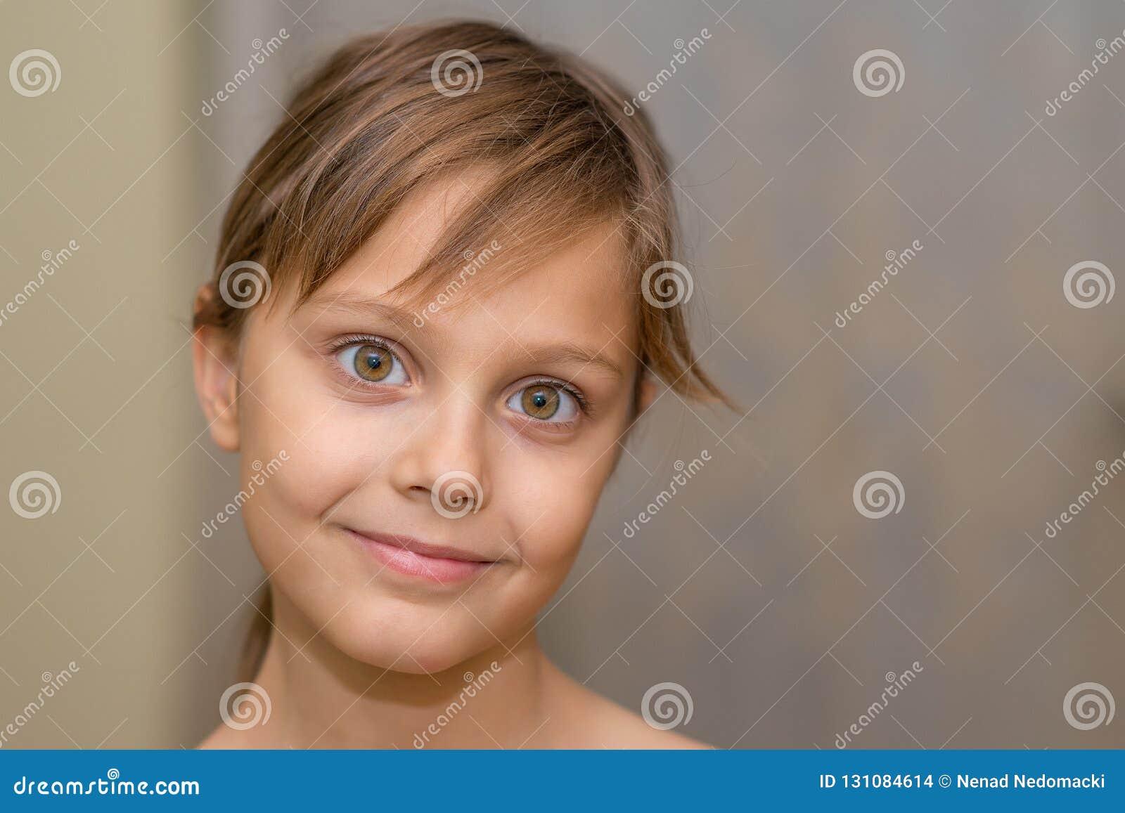 摆在照相机前面的美丽的少女