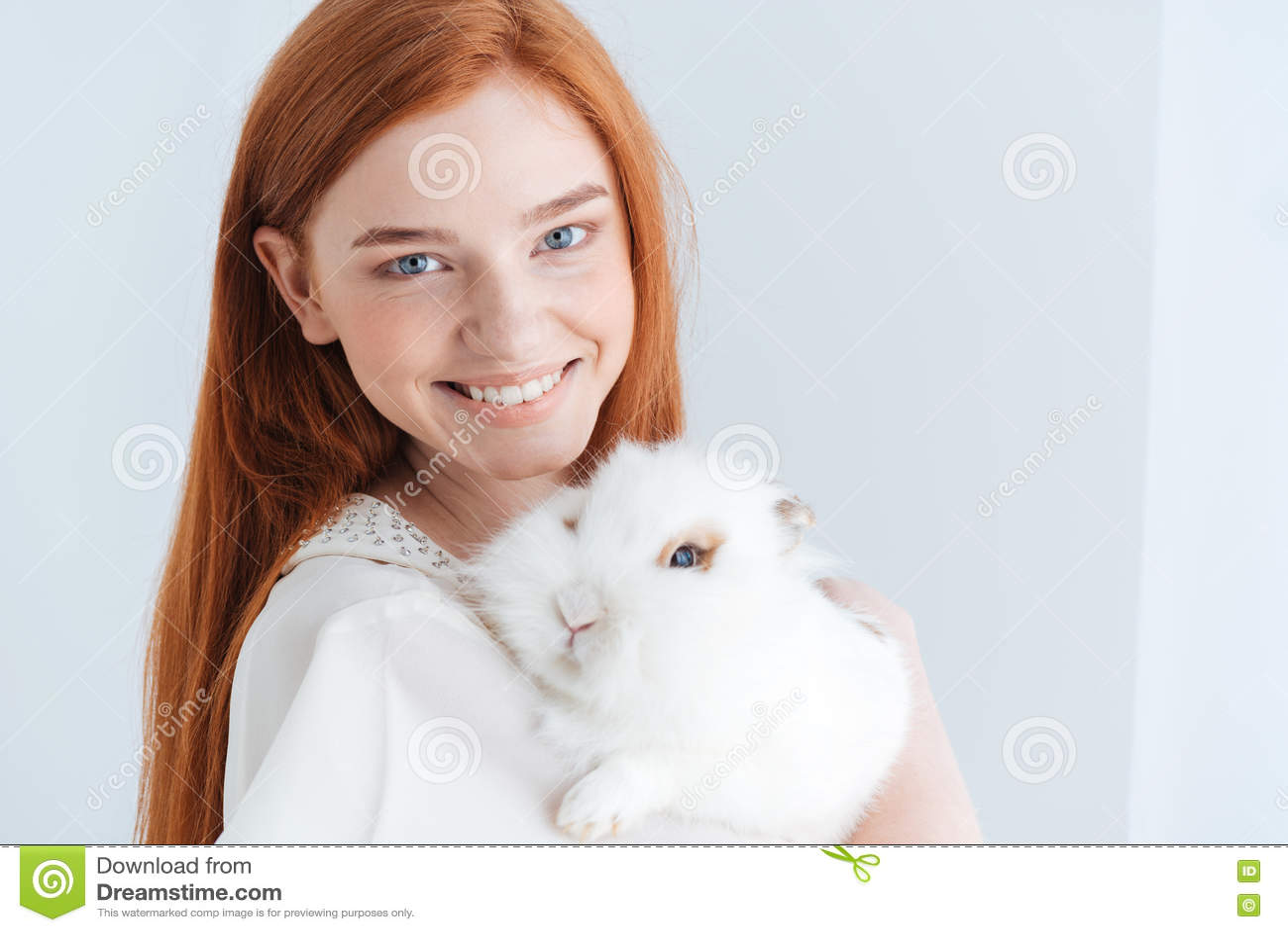 摆在用兔子的快乐的红头发人妇女