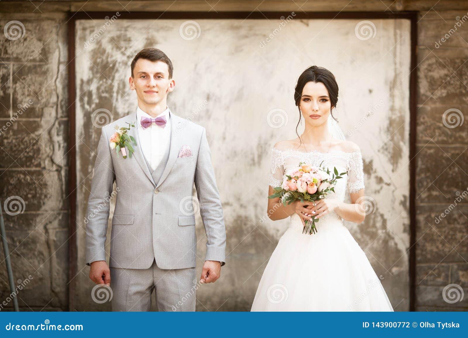 摆在老墙壁附近的美好的婚姻的夫妇
