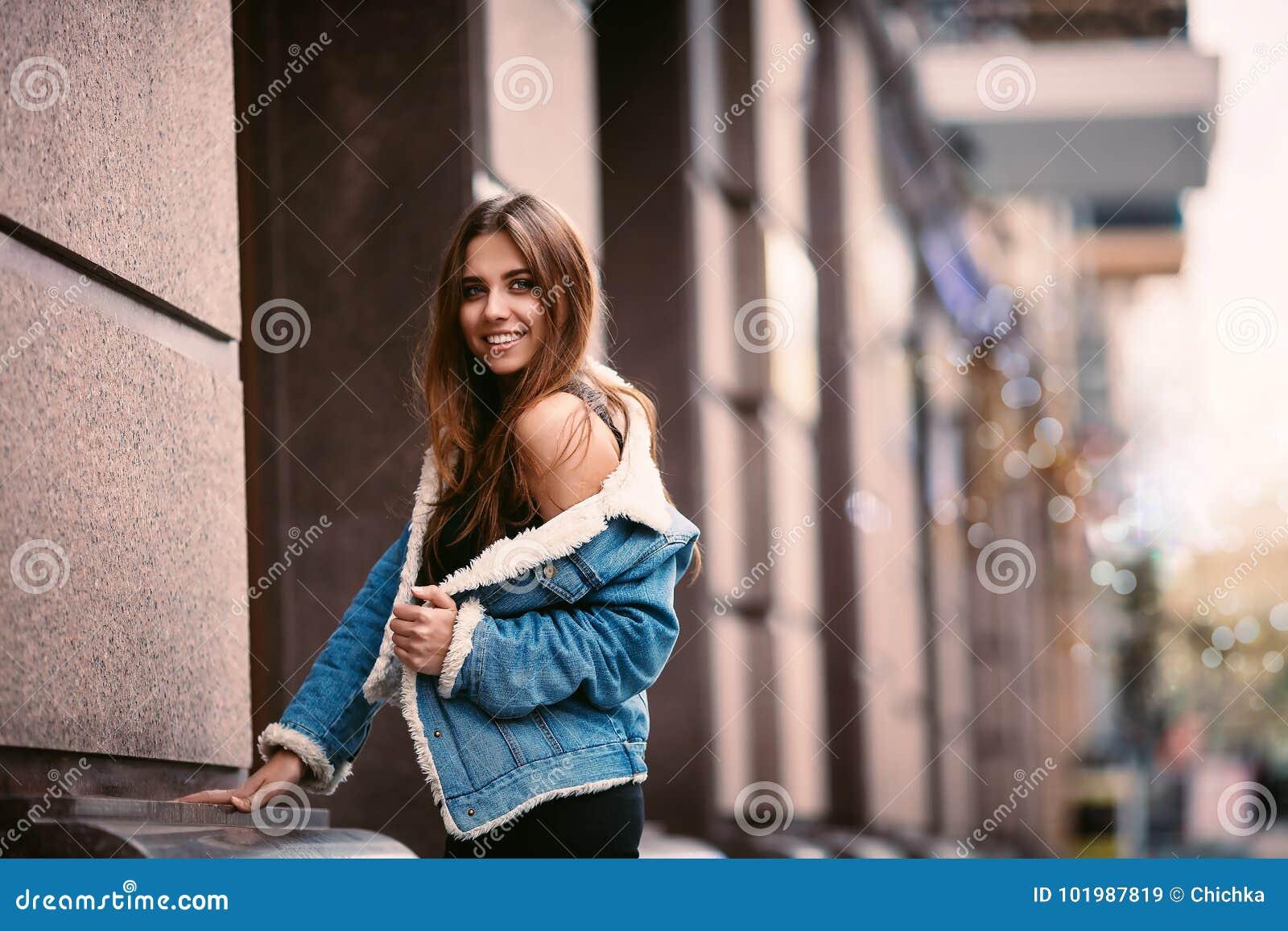 摆在街道城市的一个年轻美丽的时兴的愉快的夫人的室外画象 式样佩带的时髦的衣裳 华美的女孩