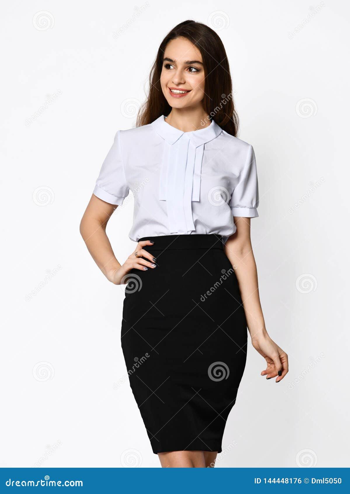 摆在轻黑暗的办公室衣服的年轻美女 轻的女衬衫和黑暗的铅笔裙子 礼服