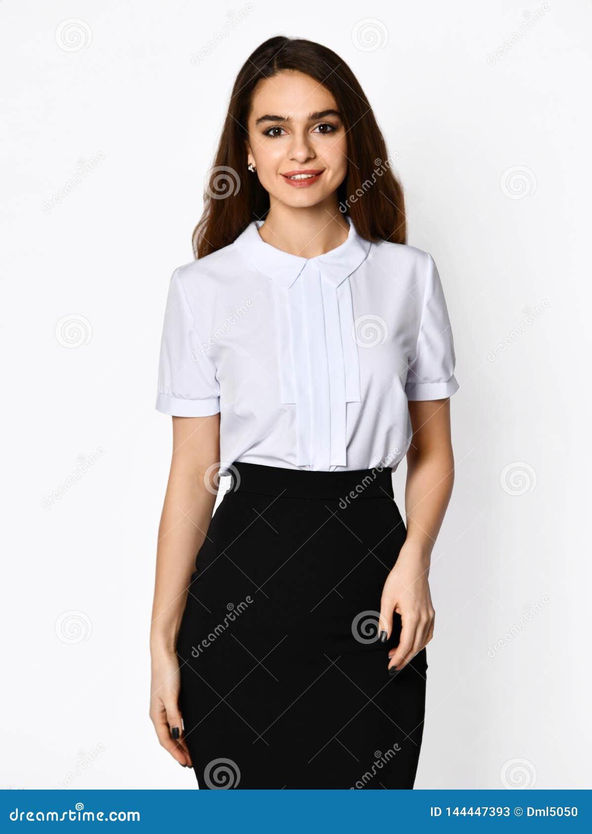 摆在轻黑暗的办公室衣服的年轻美女 轻的女衬衫和黑暗的铅笔裙子