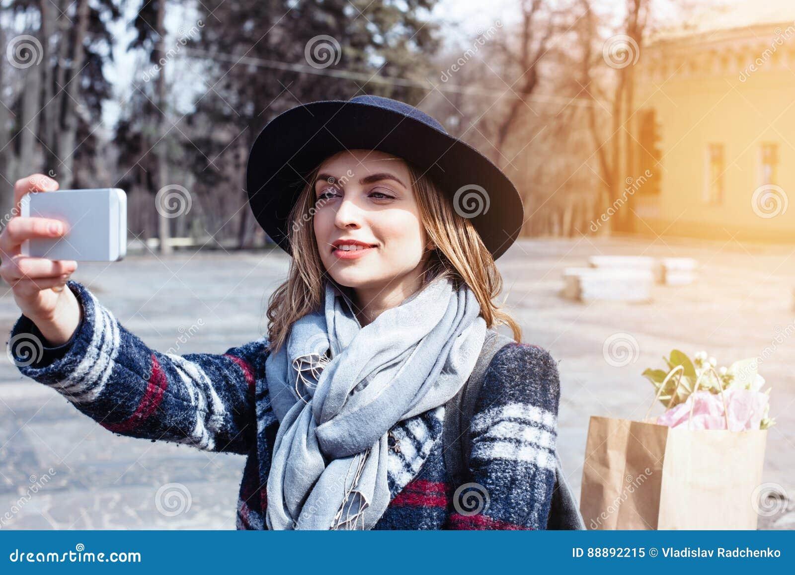 摆在年轻快乐的妇女,当拍摄在闲谈的与朋友,可爱的微笑的行家时聪明的电话照相机