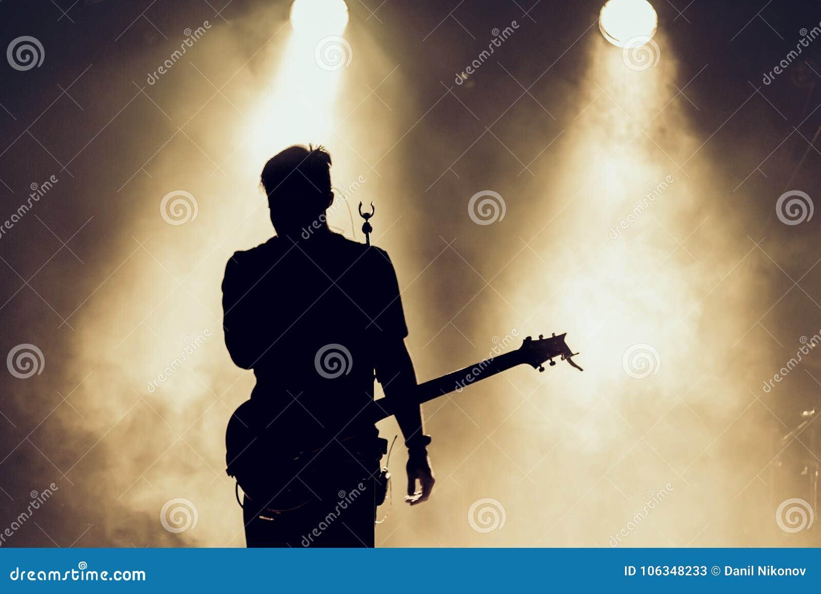 摇滚乐队在阶段执行 吉他弹奏者独奏使用 吉他演奏员剪影行动的对在音乐会人群前面的阶段 关闭