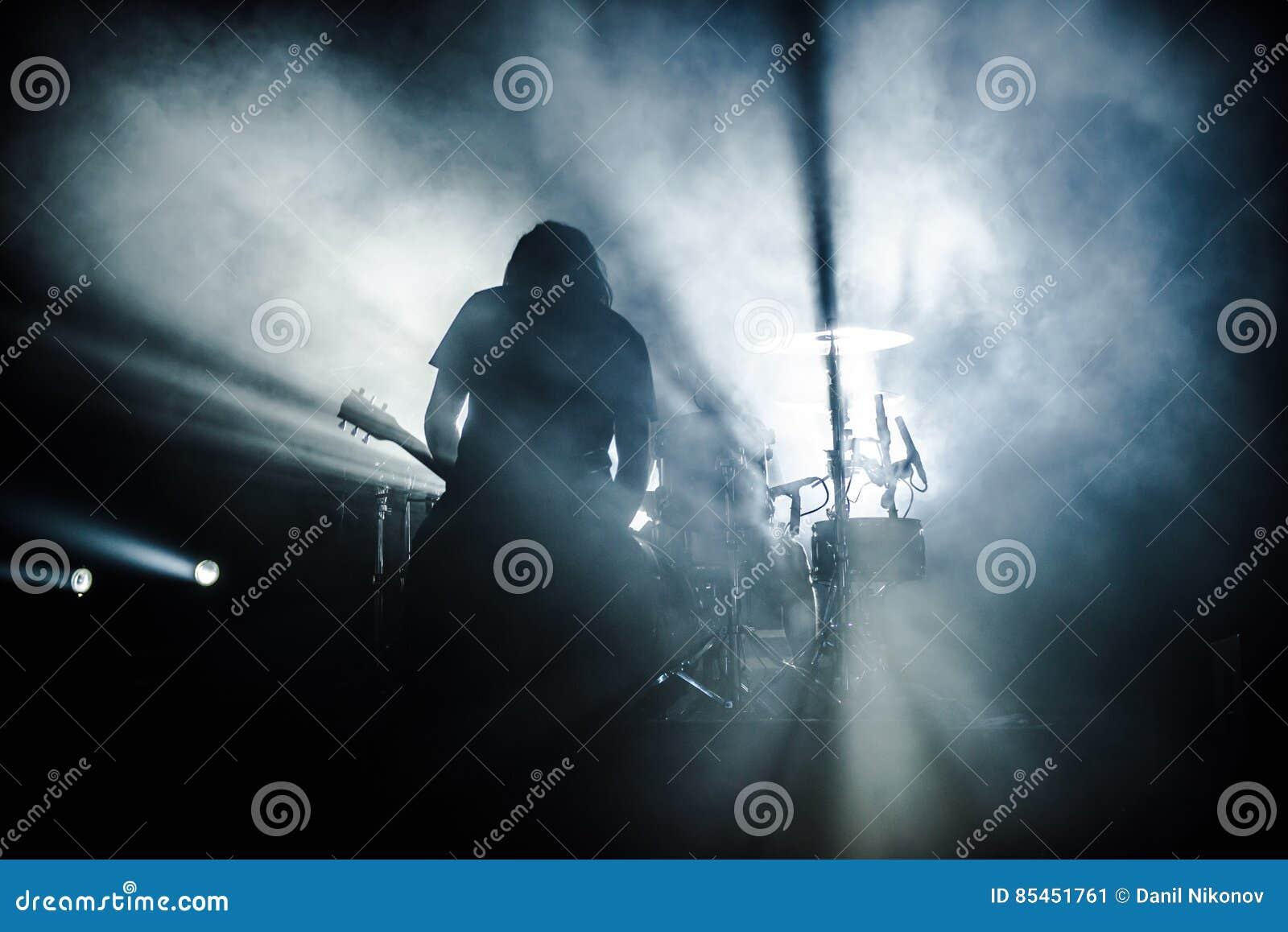 摇滚乐队在阶段执行 吉他弹奏者独奏使用 吉他演奏员剪影行动的对在音乐会人群前面的阶段