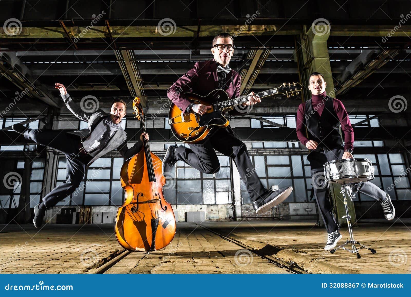 摇滚乐队跳进在一排工厂厂房的空气