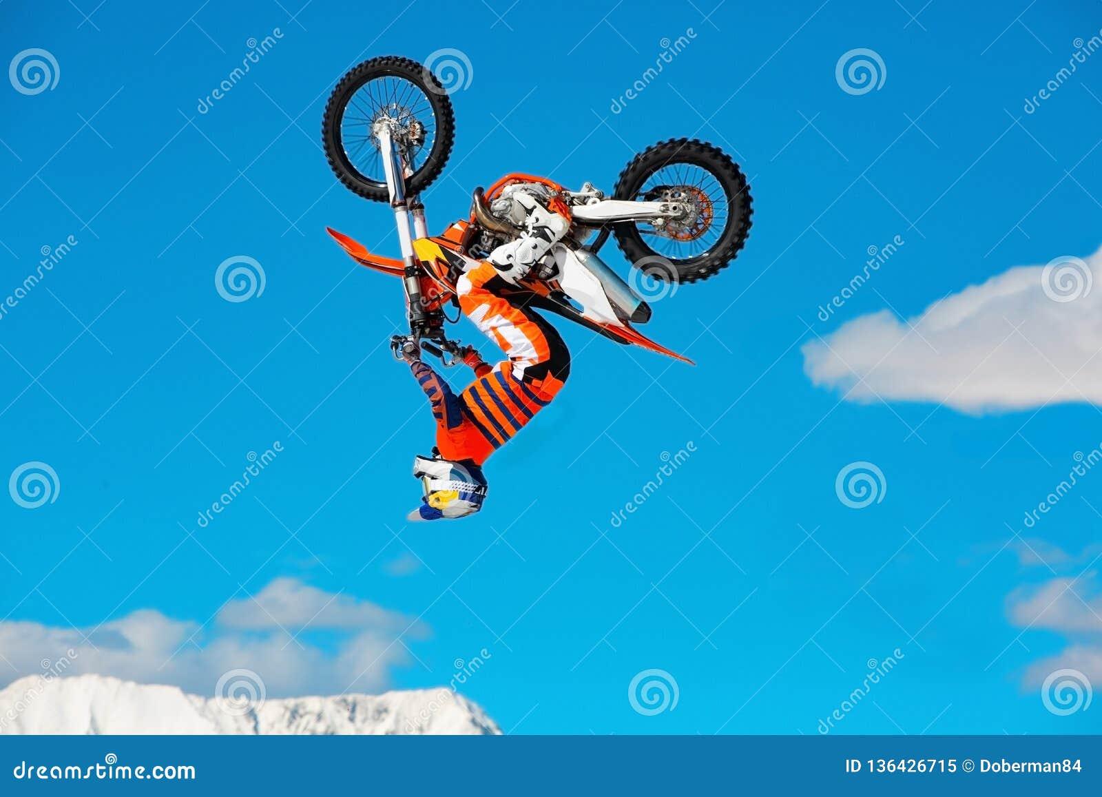摩托车的竟赛者在跳板在飞行中参加横越全国的摩托车越野赛,跳并且离开反对天空