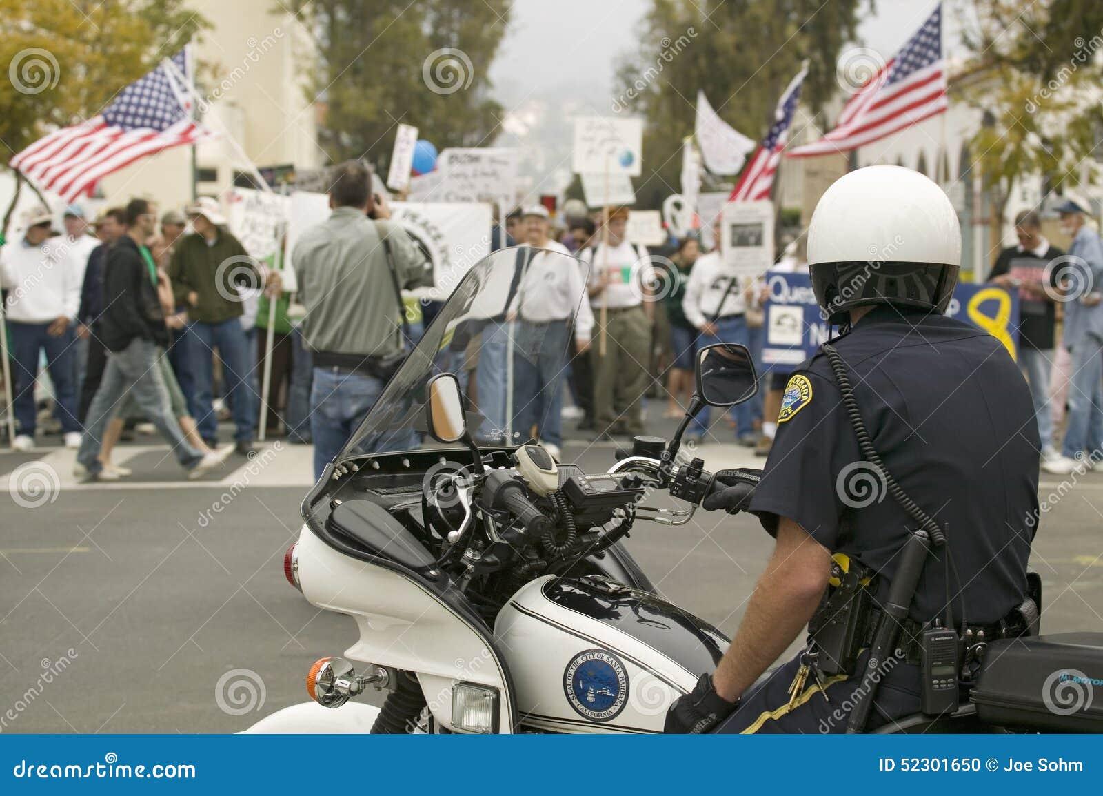 摩托车警察查看抗议者乔治W.布什和伊拉克战争反伊拉克战争抗议游行在圣芭卜拉,在2007年3月17日的加利福尼亚 布什和伊战在反伊拉克战争抗议游行在圣诞老人巴勃