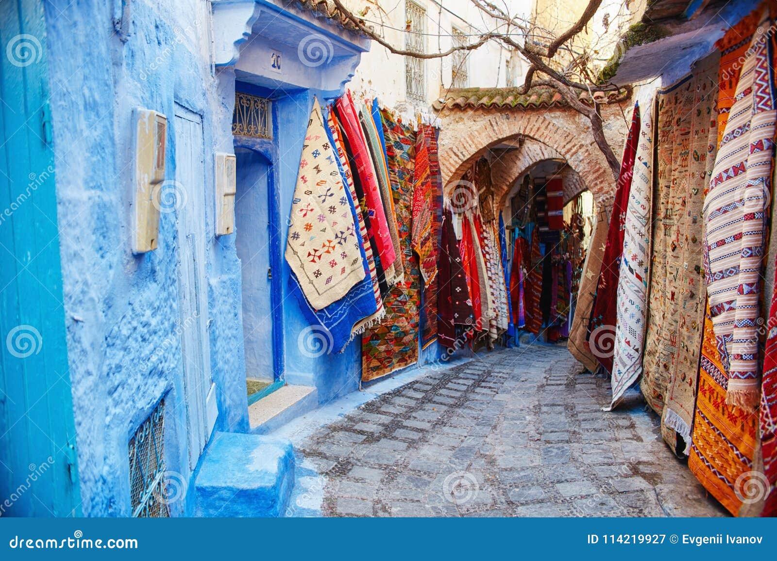 摩洛哥是蓝色市舍夫沙万,在蓝色颜色绘的不尽的街道 许多花和纪念品在美丽