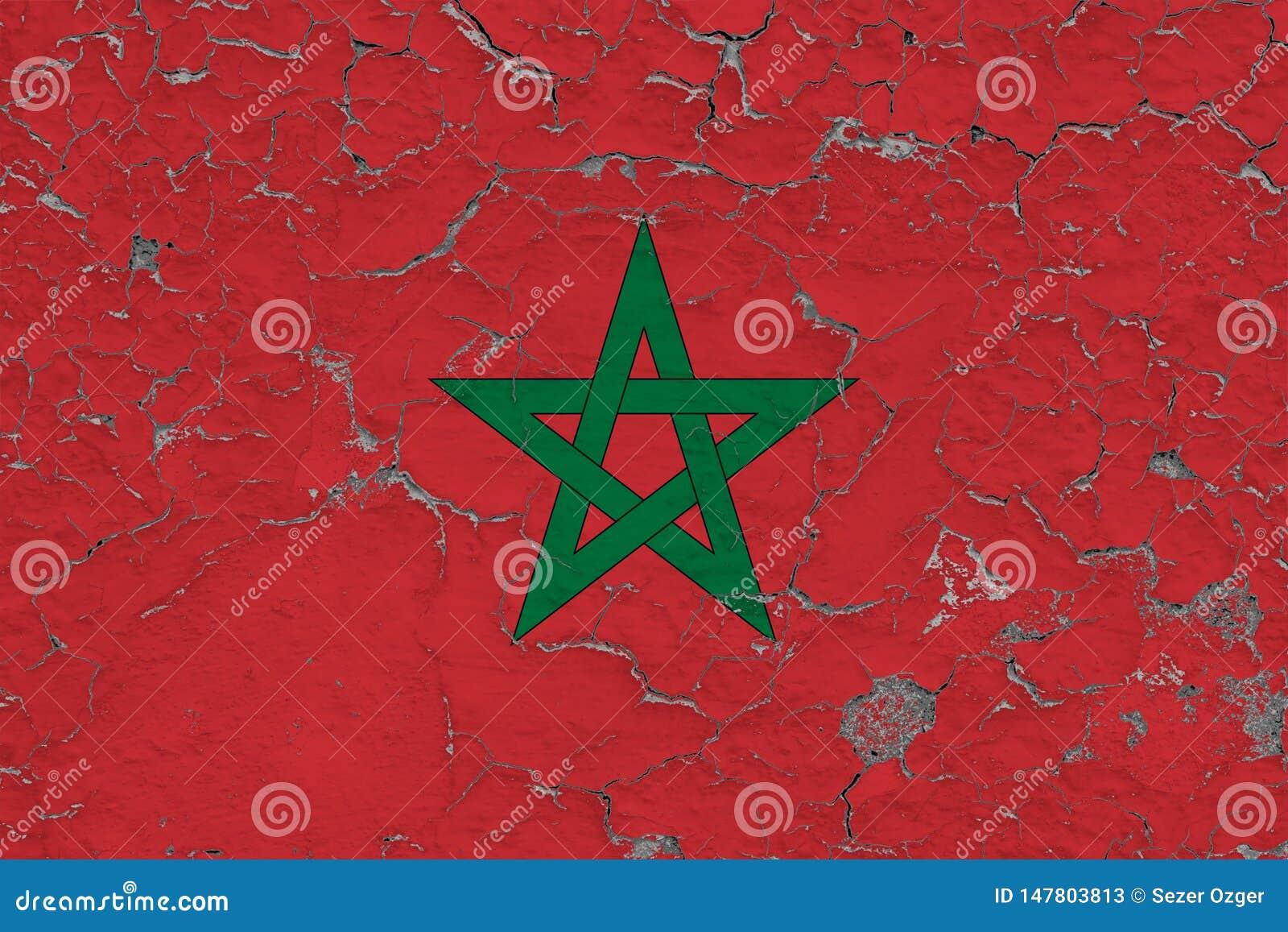 摩洛哥的旗子在破裂的肮脏的墙壁上绘了 葡萄酒样式表面上的全国样式