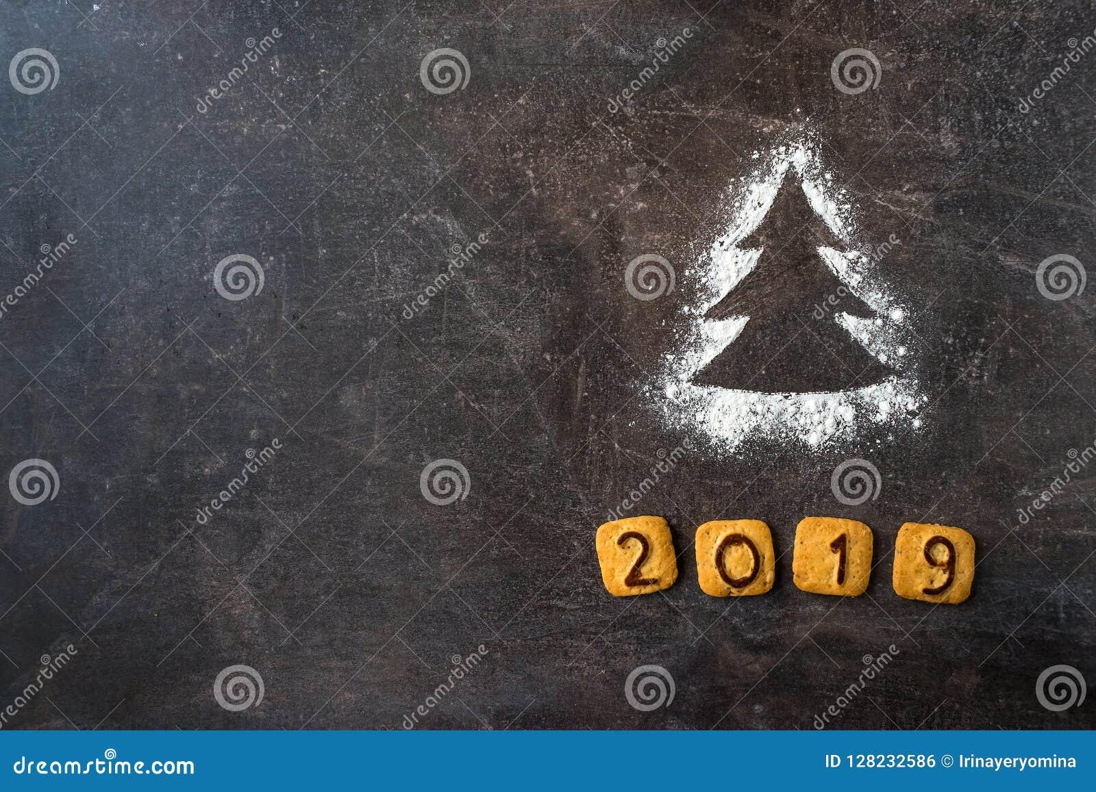 撒粉于剪影与曲奇饼数字的圣诞树2019年在黑暗