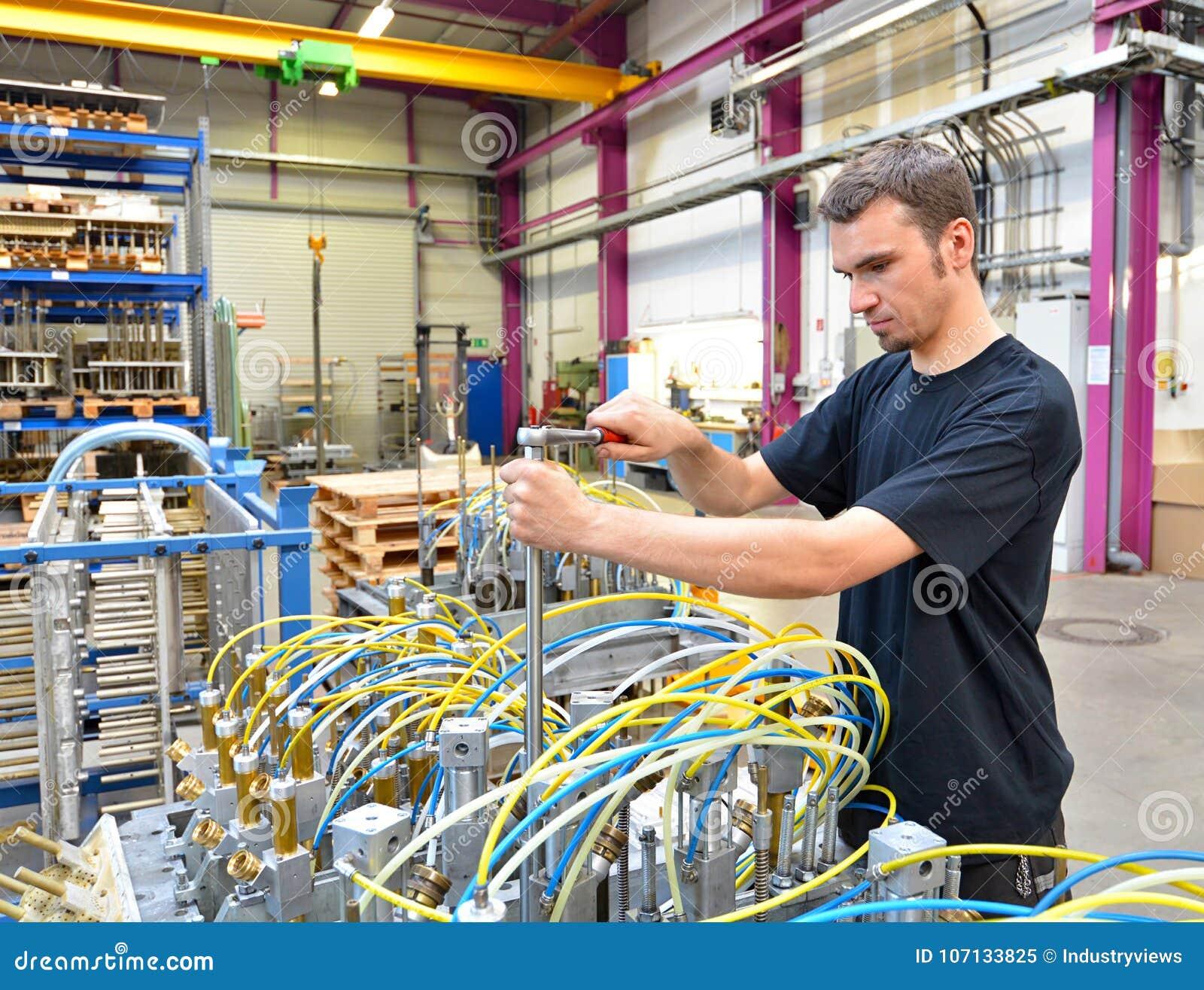操作员在有工具的一套工厂设备- p修理一个机器