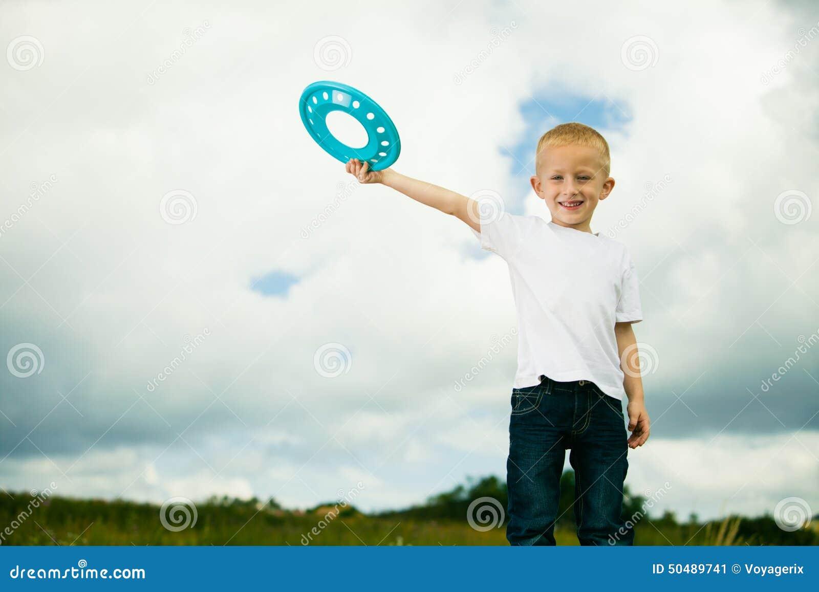 操场孩子的孩子在使用与飞碟的行动男孩