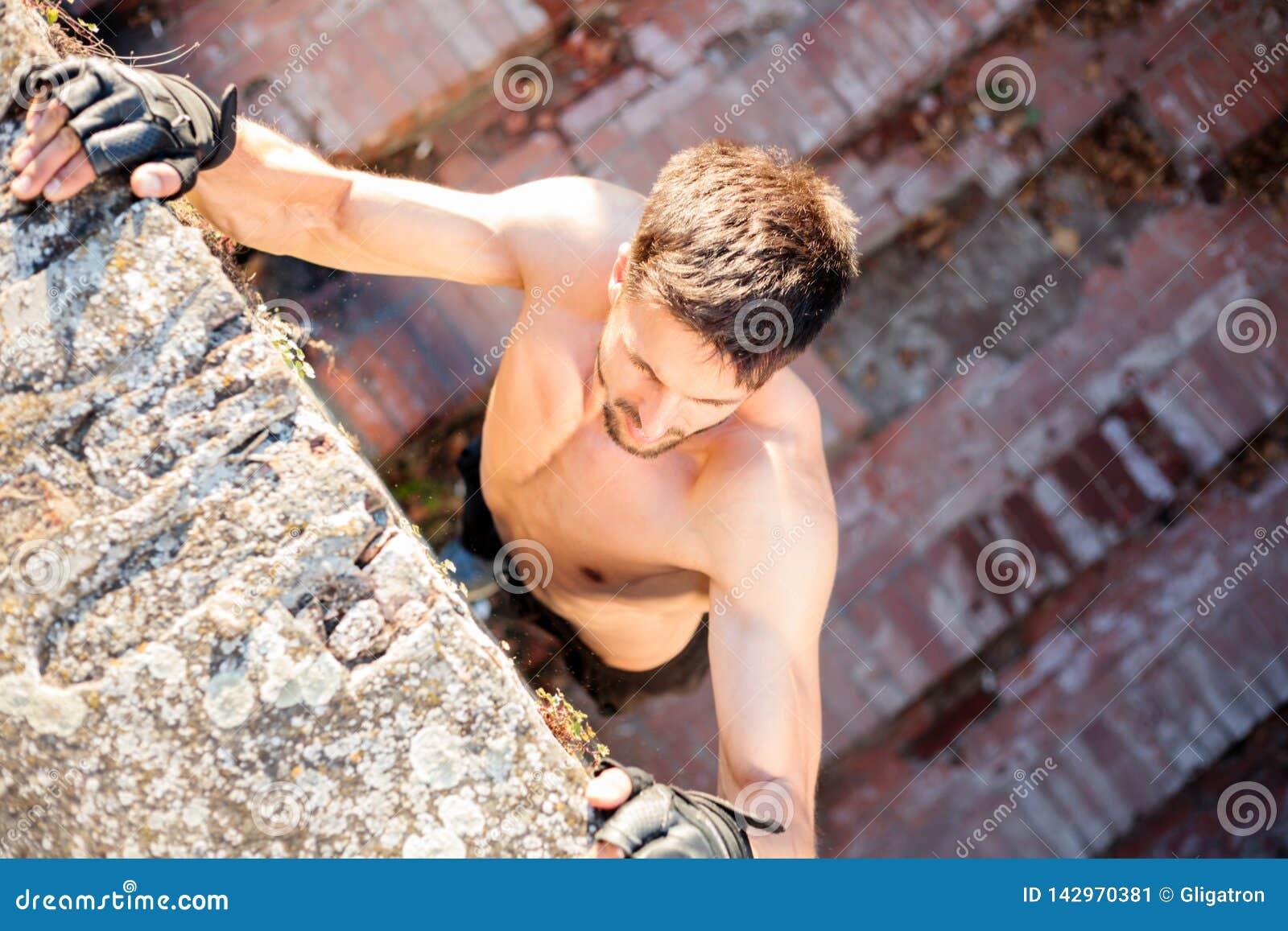 攀登墙壁的坚定的年轻人,当自由赛跑时
