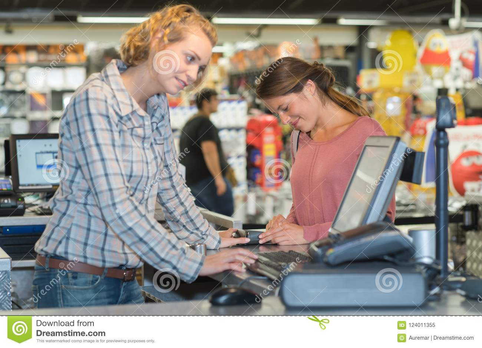 支付在有终端的收银处的女性顾客在超级市场