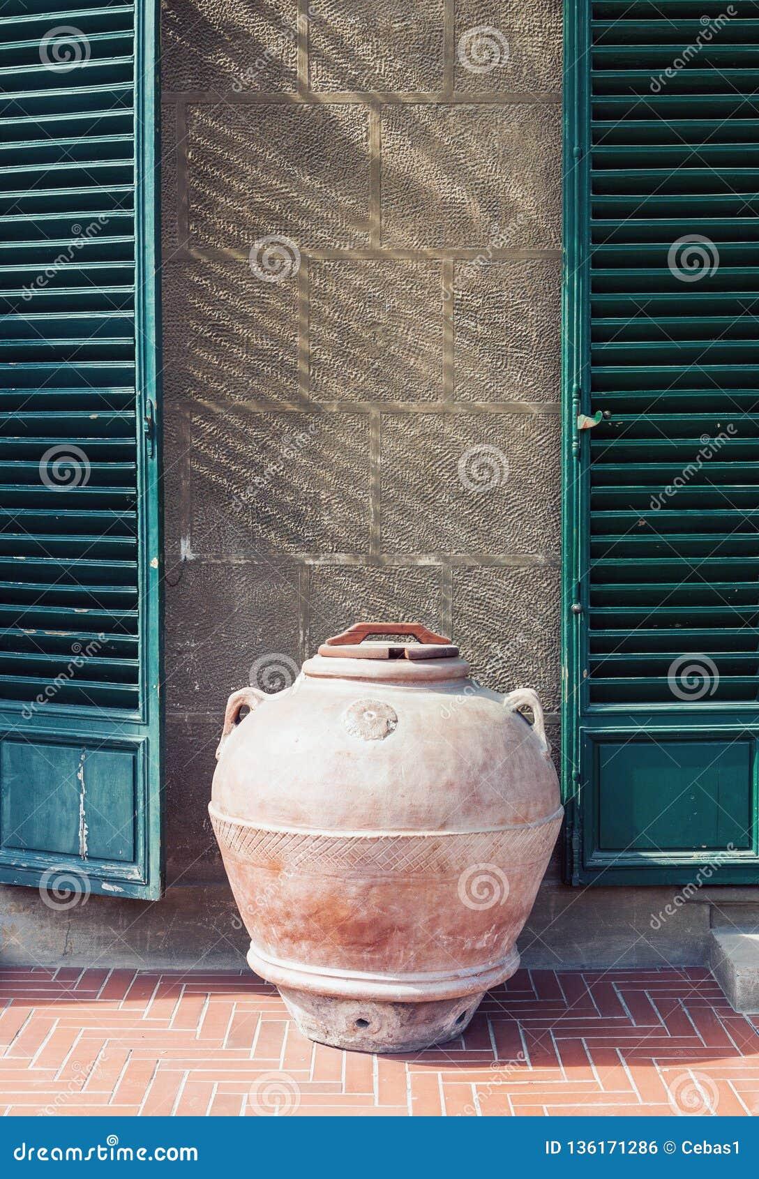支持一个老房子的墙壁的古色古香的黏土瓶子在意大利