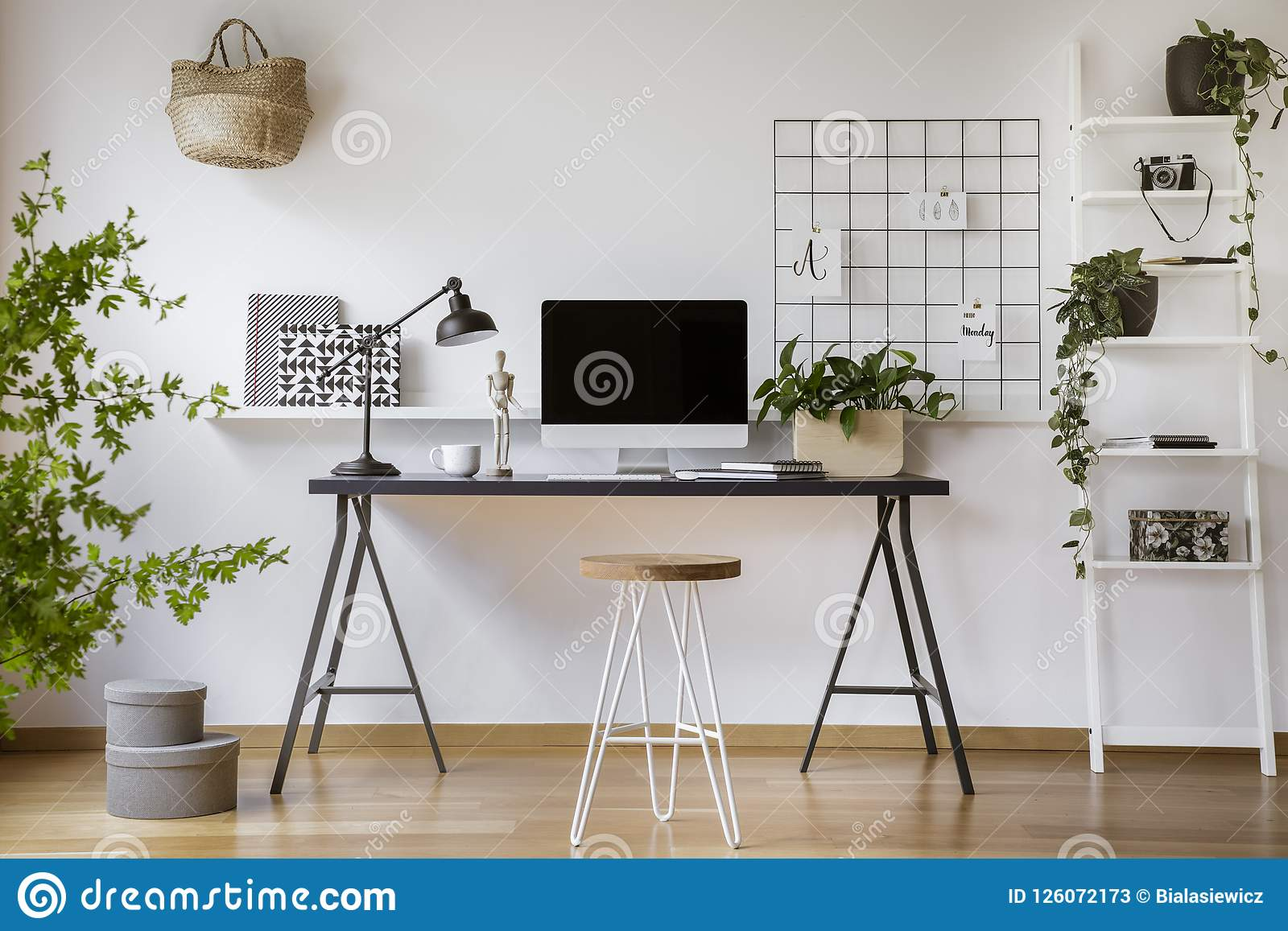 支持有大模型屏幕、金属灯和咖啡杯的簪子凳子木书桌在真正的照片白色家庭offic