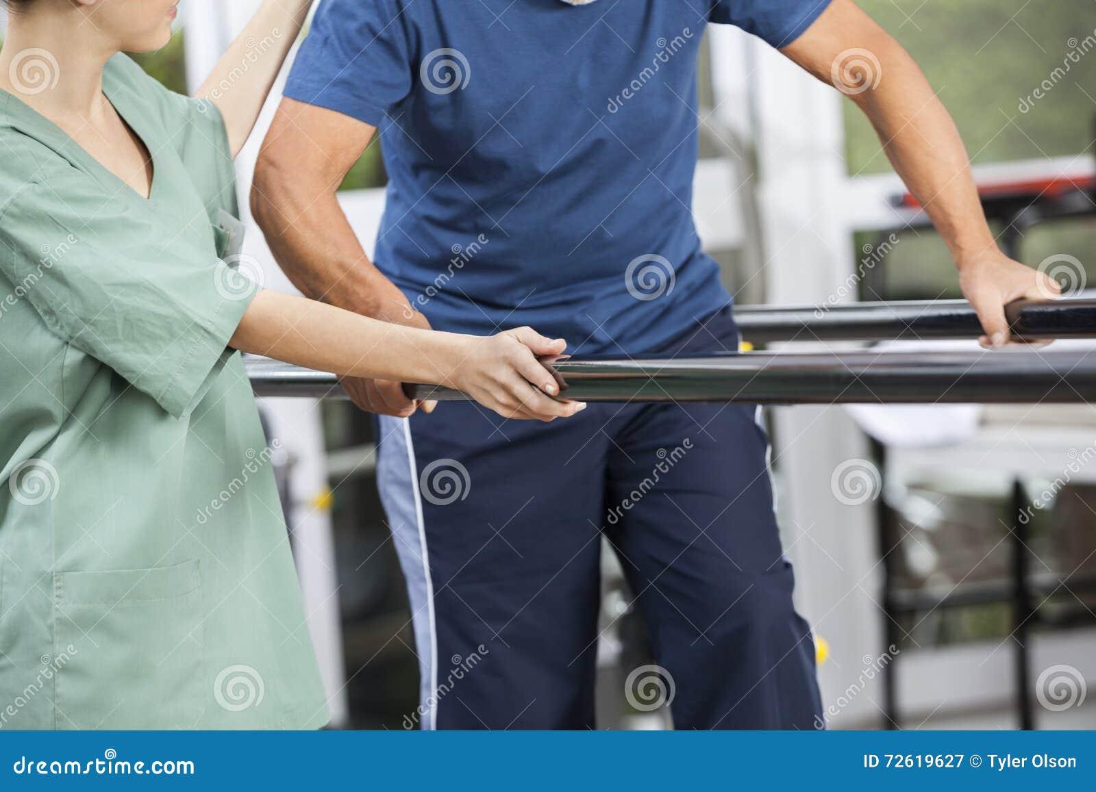 支持老人的生理治疗师走在平行之间
