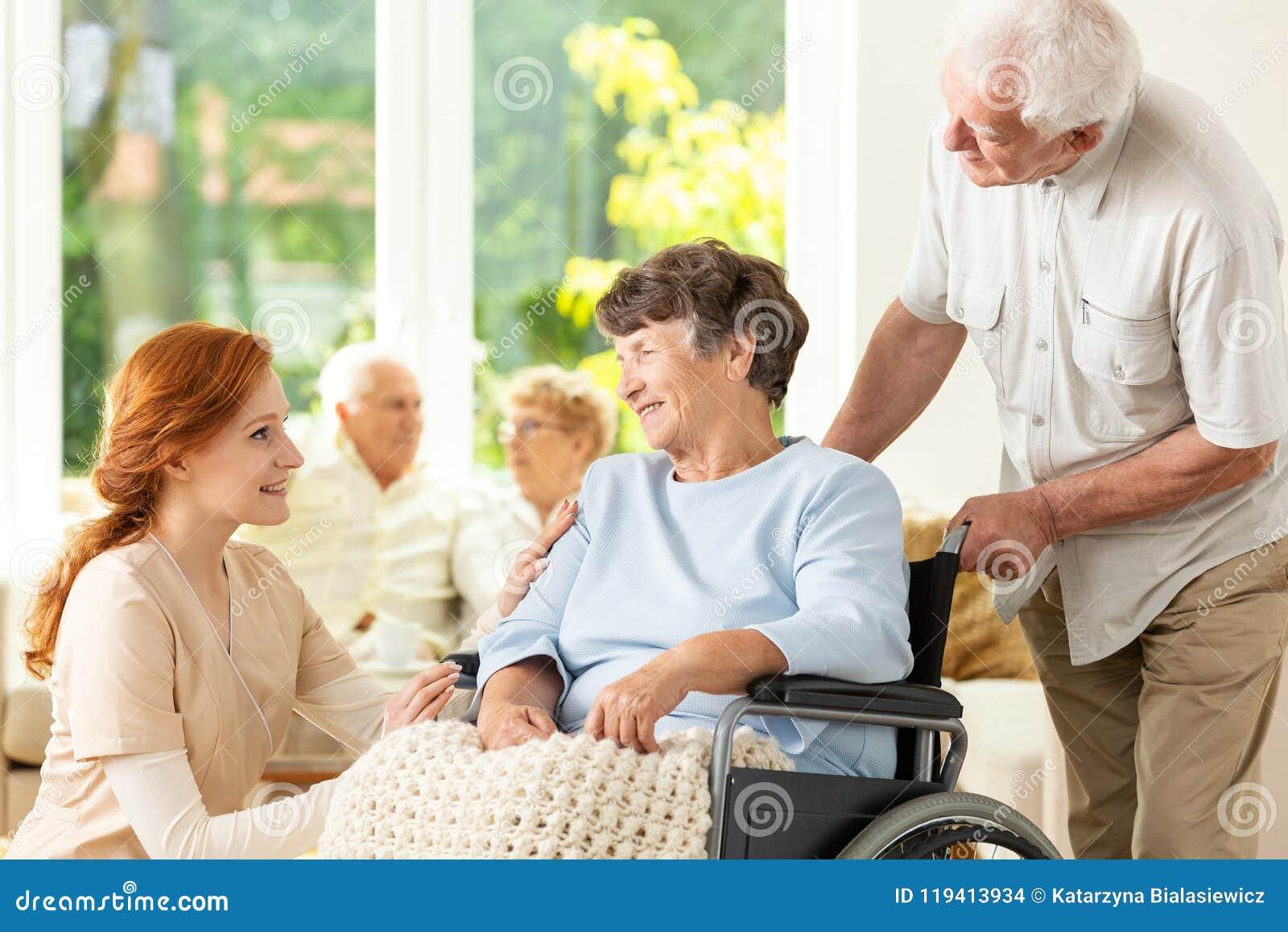 支持被麻痹的年长妇女的微笑的护士和老人