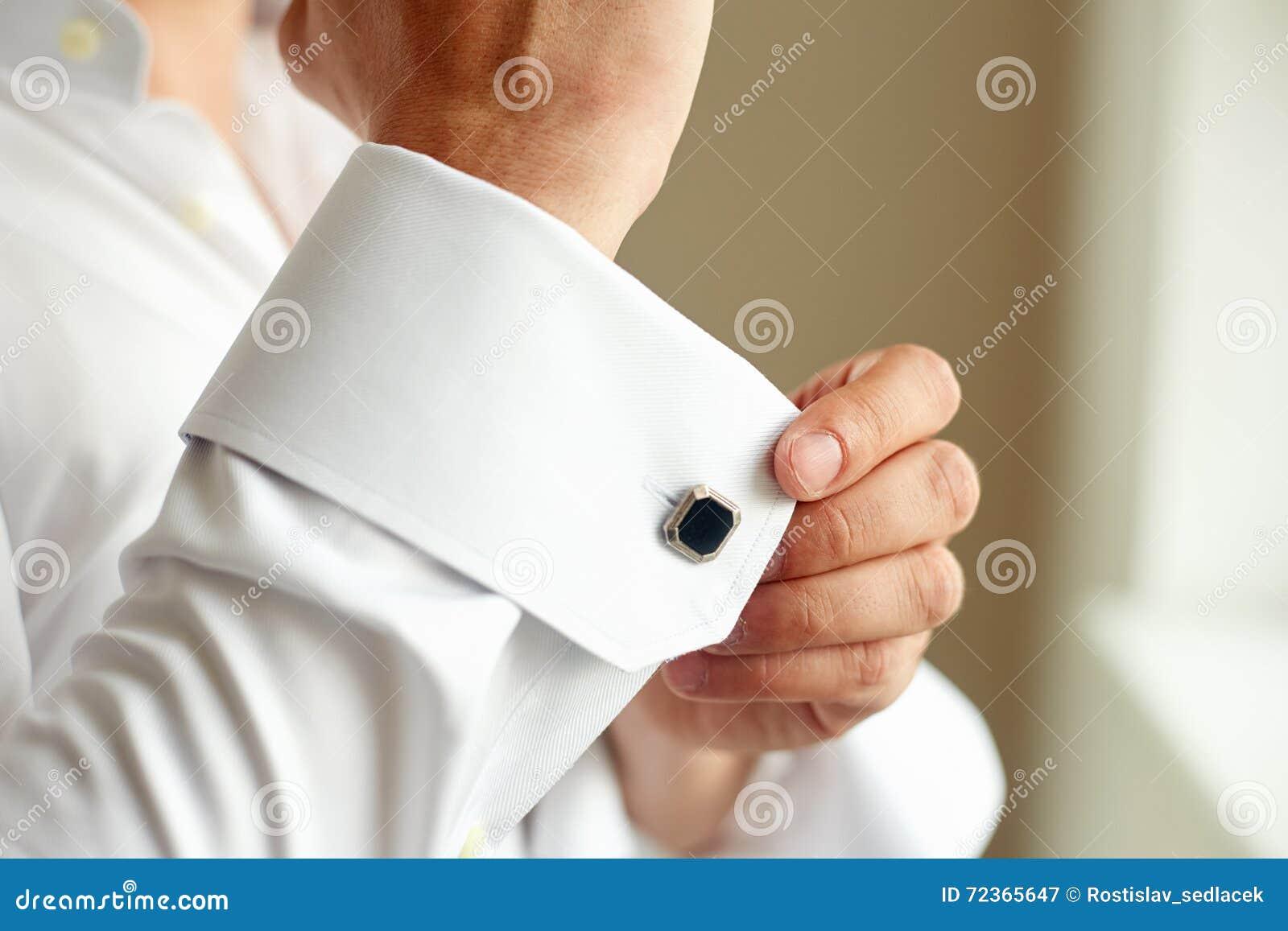 改正他的衬衣的袖子人