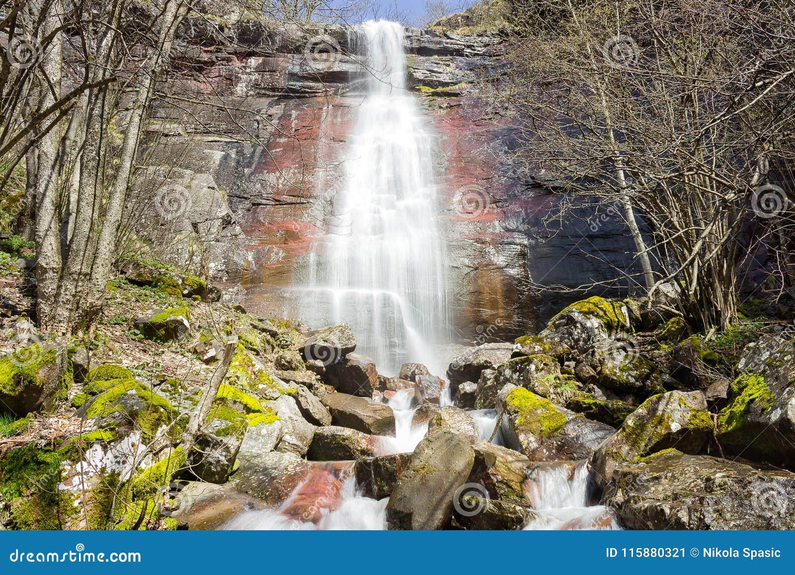 放出在红色峭壁下的强有力,被日光照射了瀑布