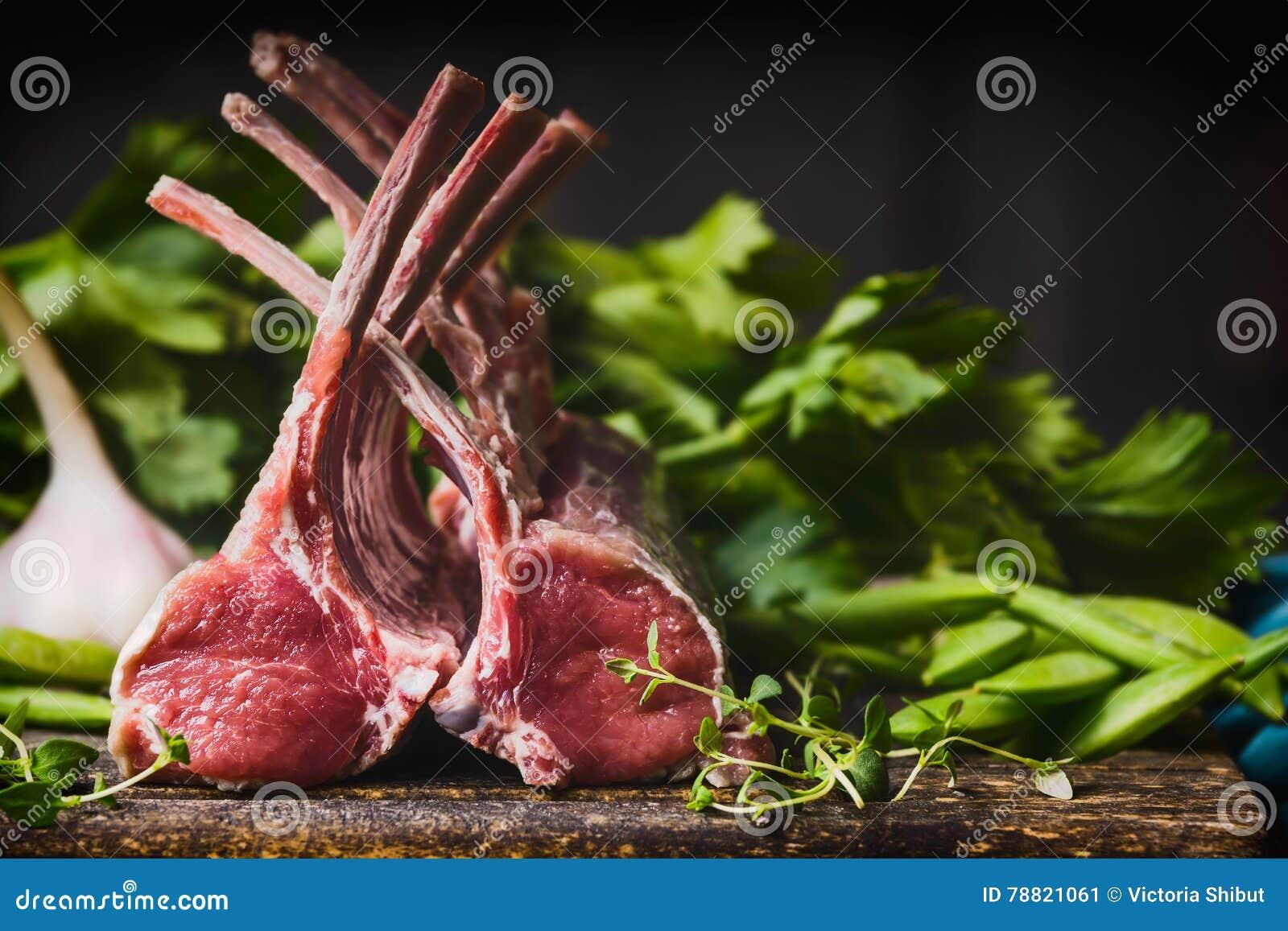 放在架子上的羊羔,与骨头的生肉在木背景的土气厨房用桌上