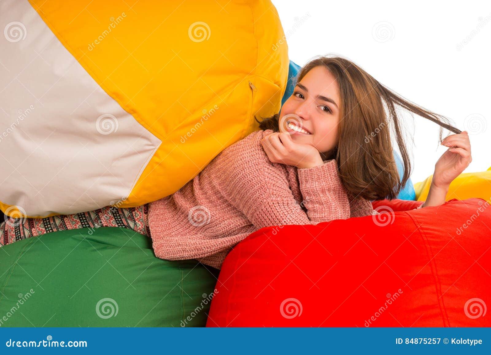 放在装豆子小布袋椅子之间的年轻愉快的妇女