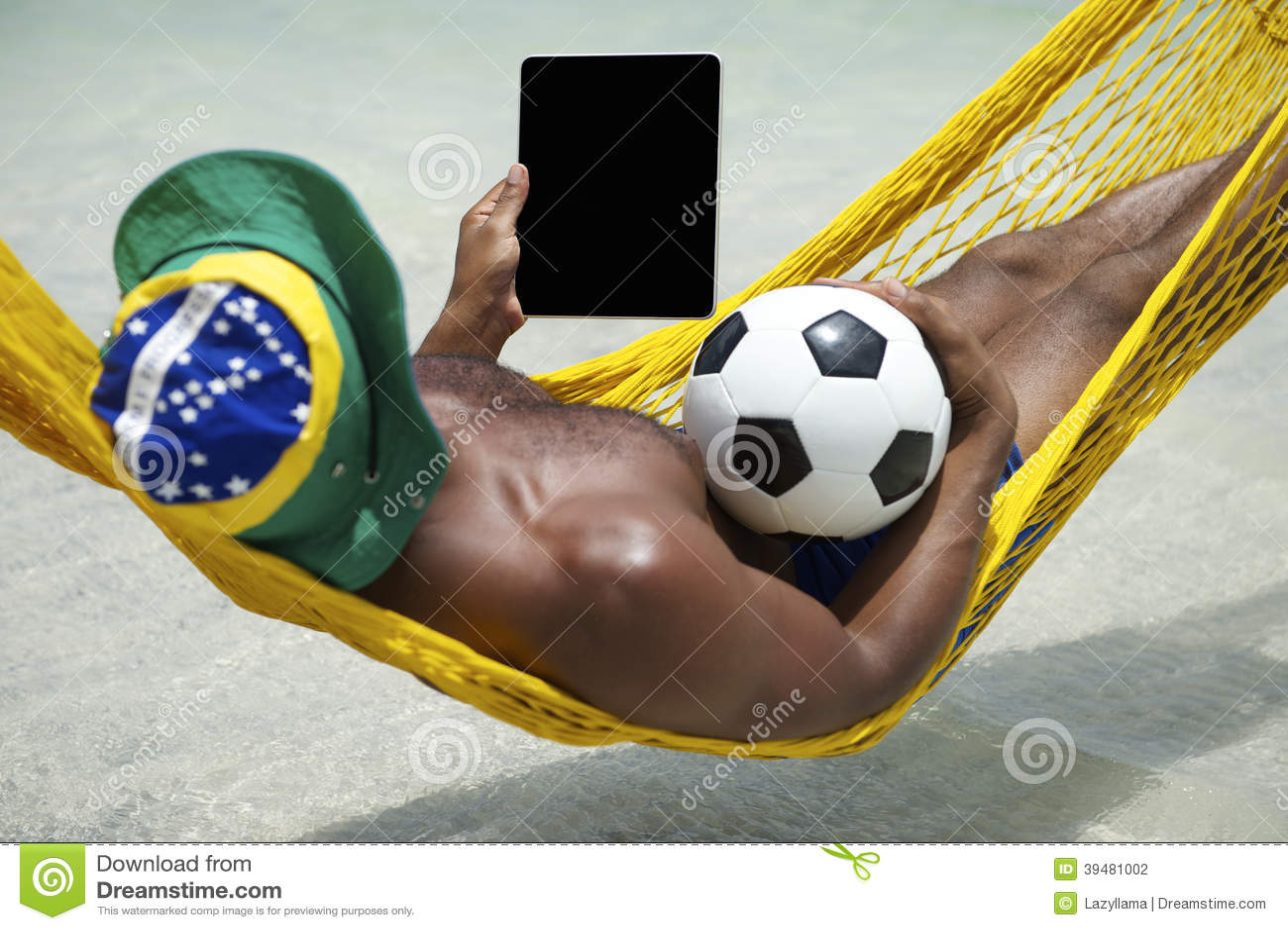 放松与片剂和橄榄球海滩吊床的巴西人