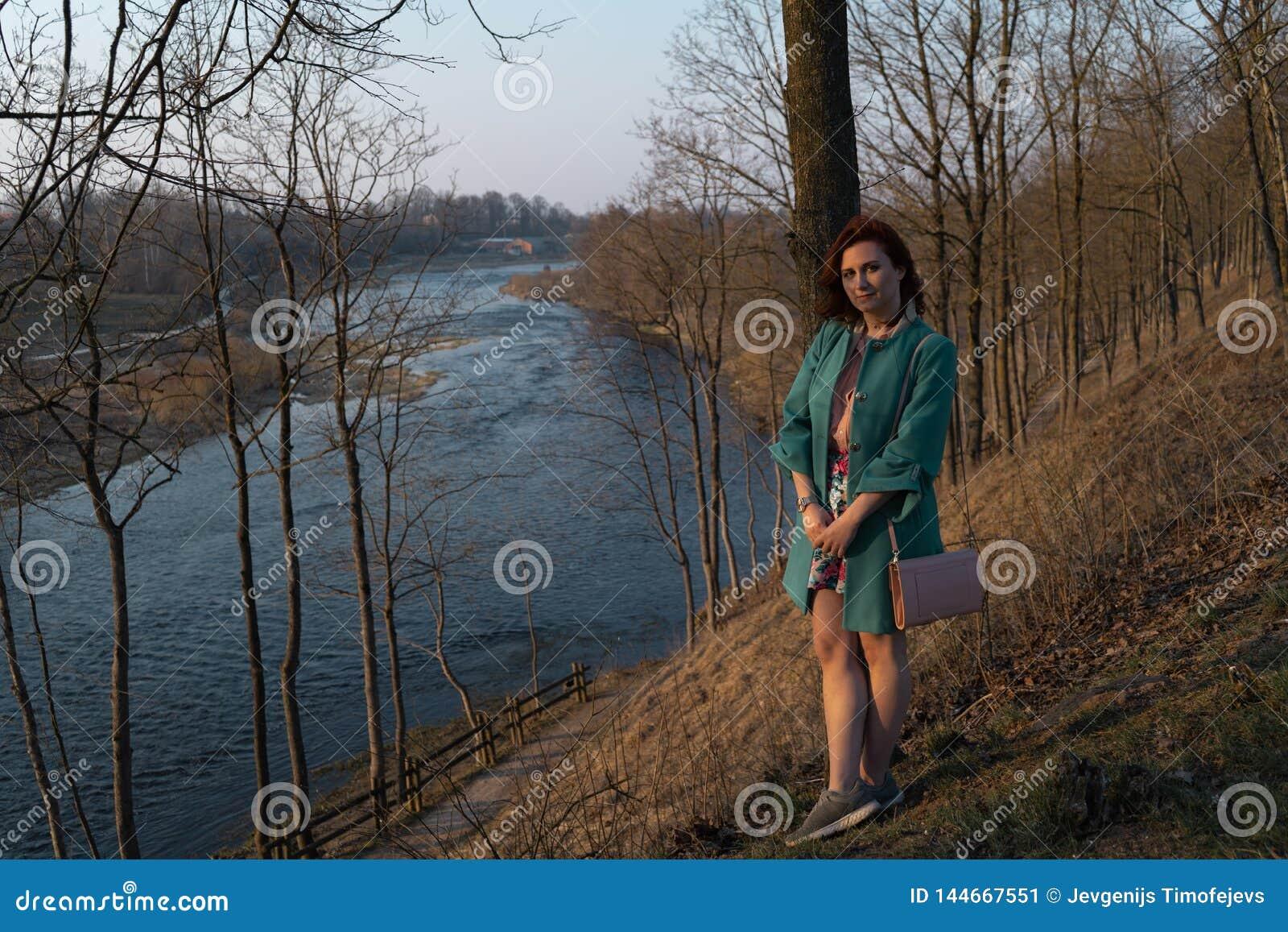 放松和享受日落的年轻时尚妇女在一条河附近在包斯卡,拉脱维亚,2019年