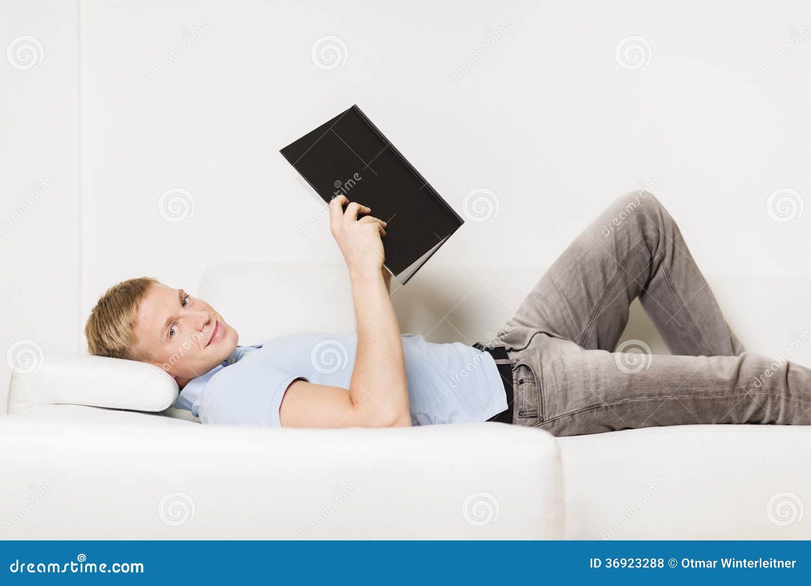 放松和读书的微笑的年轻人在沙发。