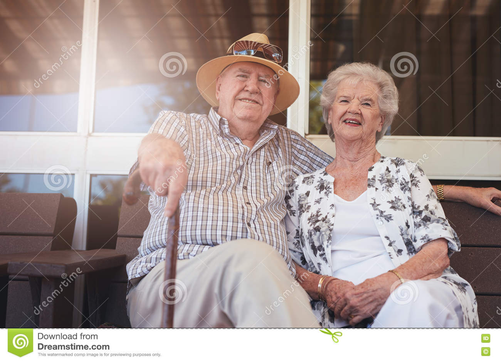 放松在一条长凳的爱的退休的夫妇他们的房子外