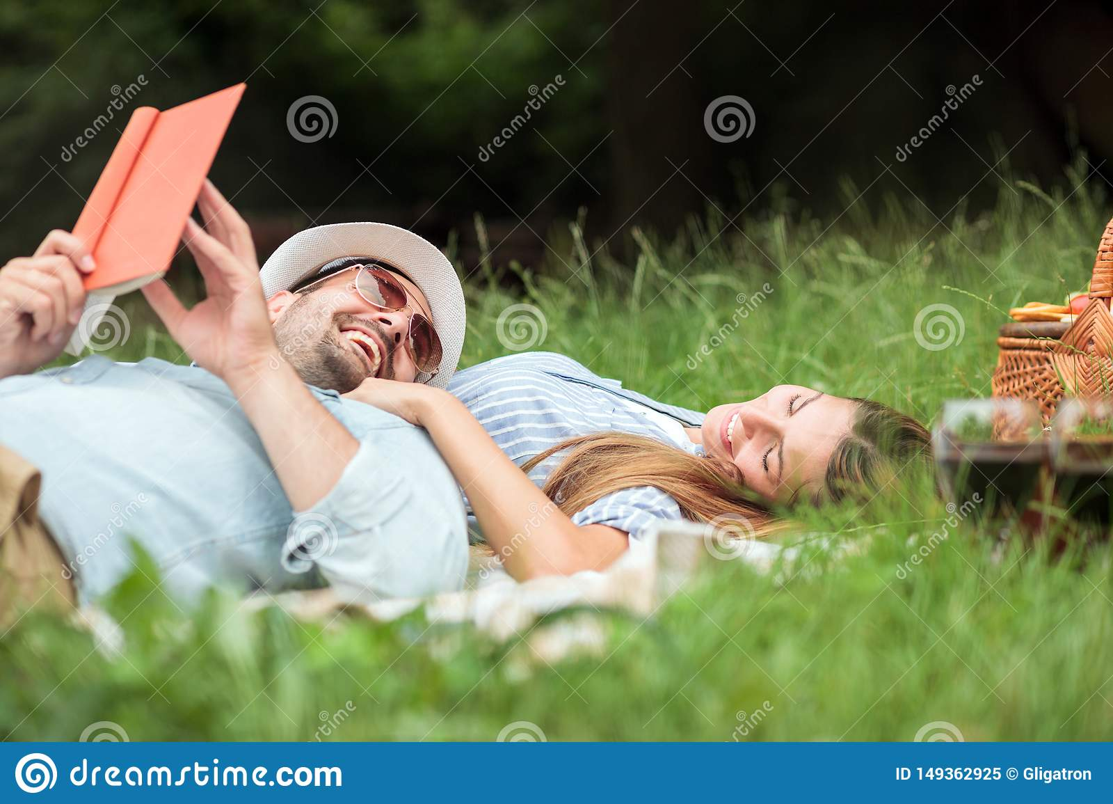 放松在公园的愉快的微笑的年轻夫妇 说谎在野餐毯子