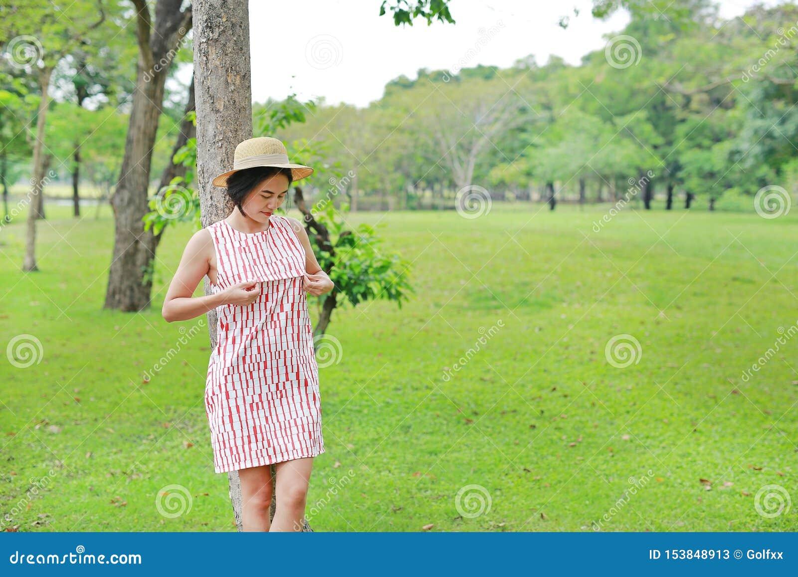 放松在夏天庭院里的年轻亚裔妇女