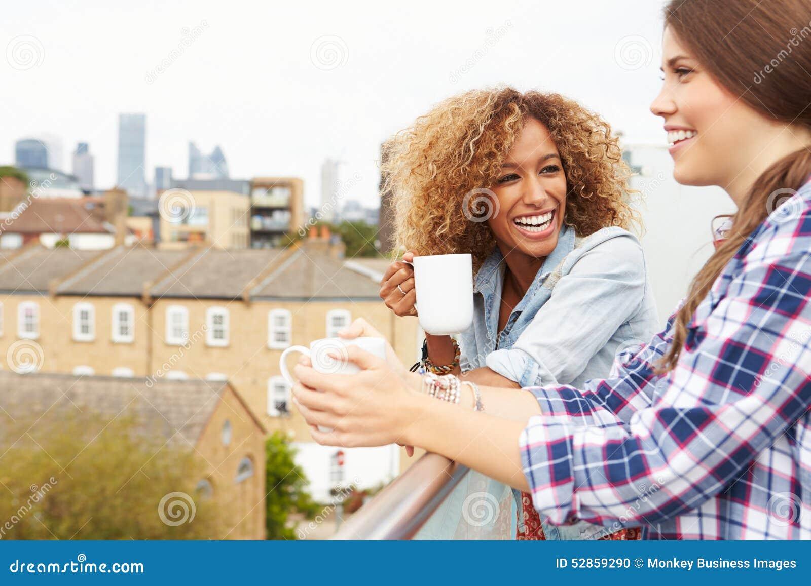 放松在屋顶庭院饮用的咖啡的两名妇女