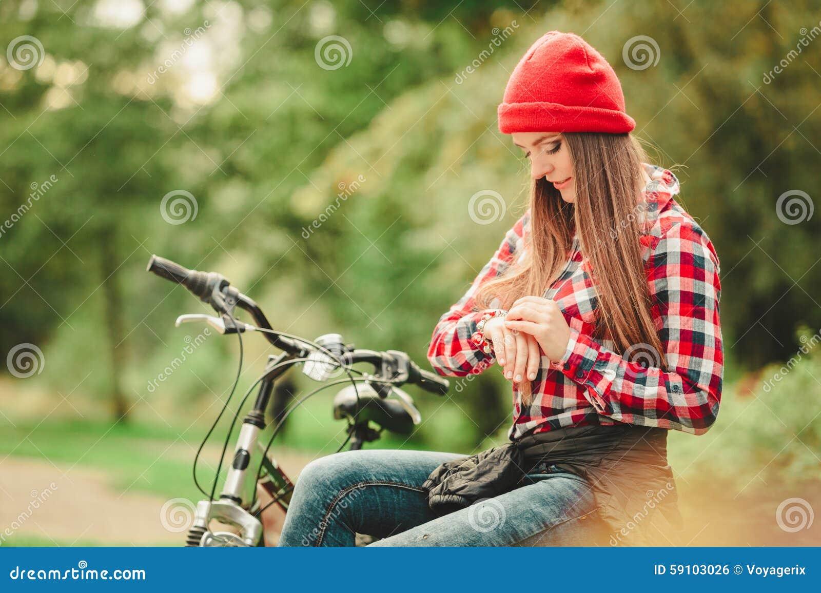 放松在有自行车的秋季公园的女孩