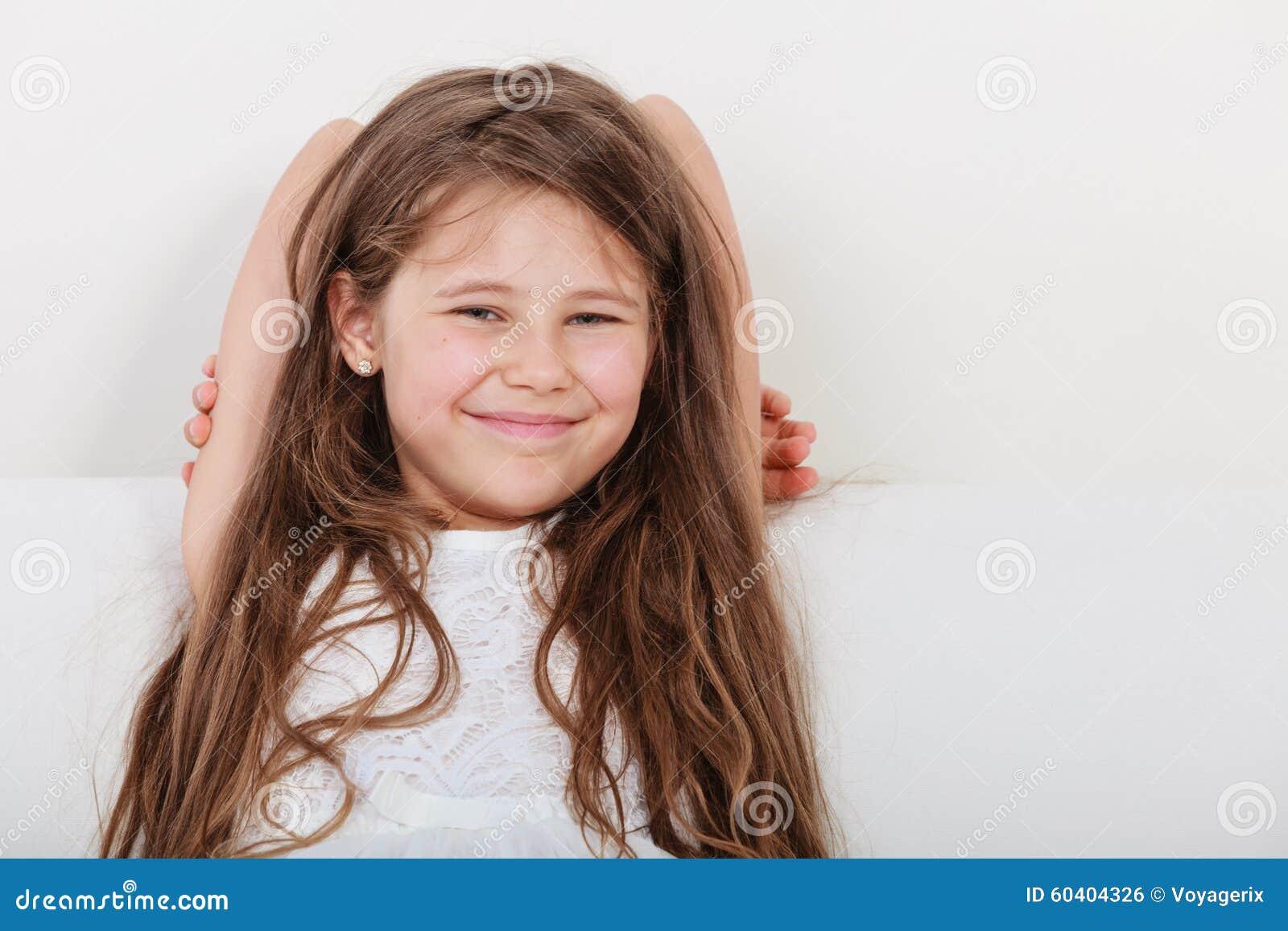 放松在沙发的愉快的小女孩孩子