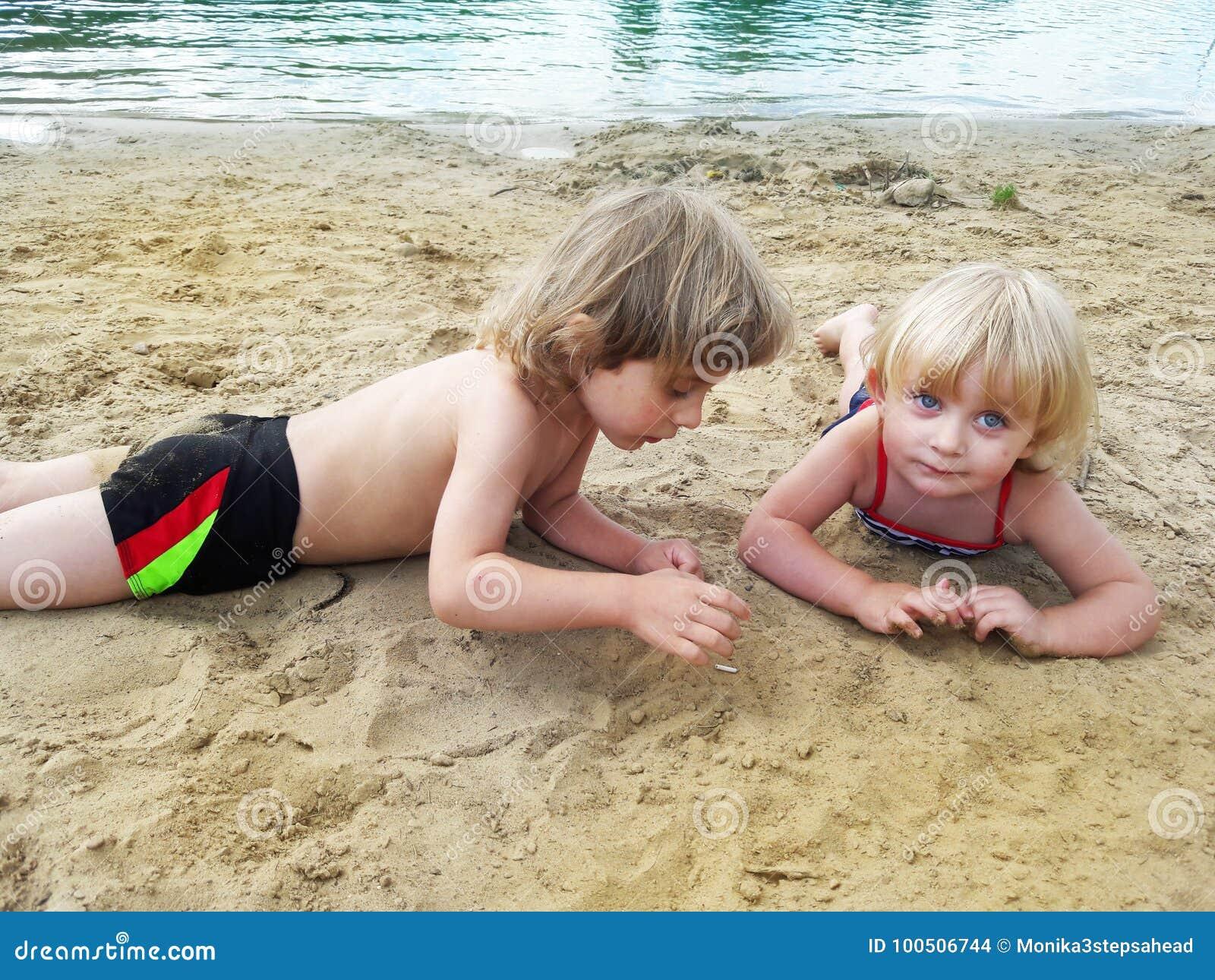 放松在沙子的兄弟和姐妹在湖附近