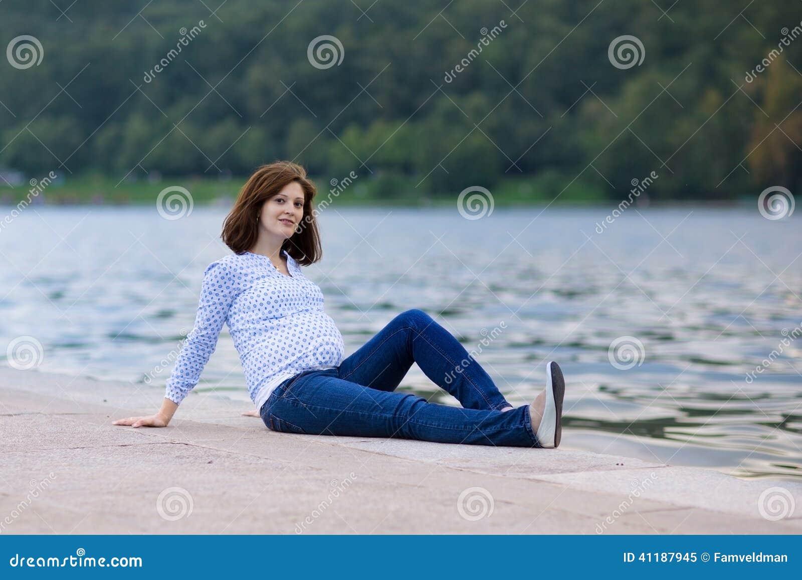 放松在河岸的美丽的孕妇