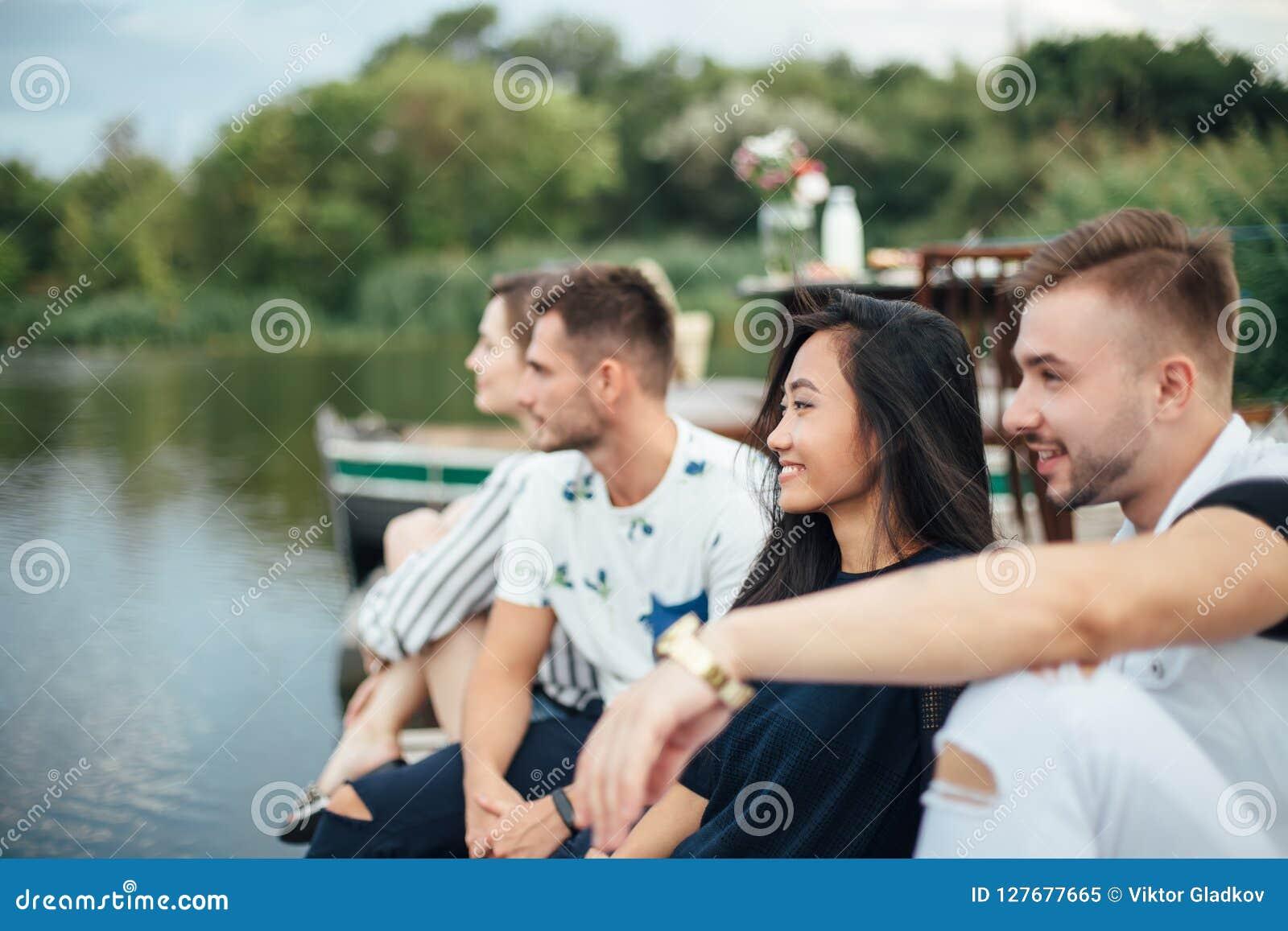 放松在河码头的小组愉快的年轻朋友