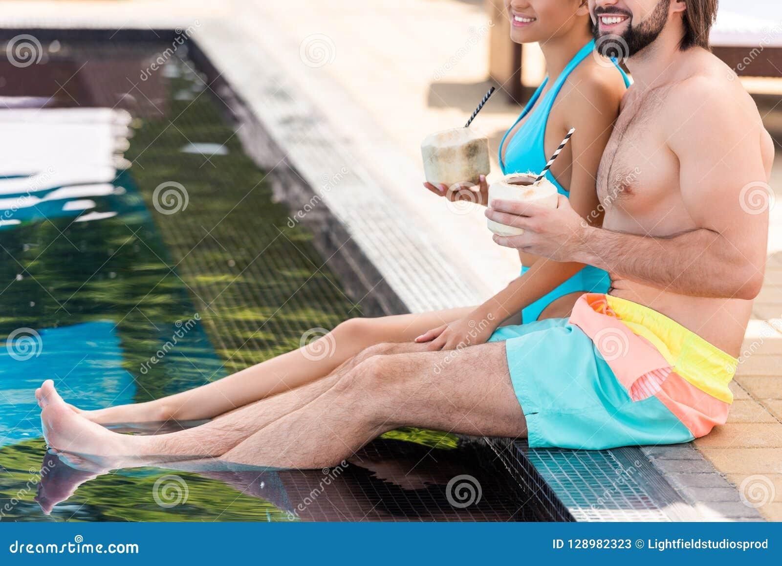 放松在游泳场附近的夫妇播种的看法