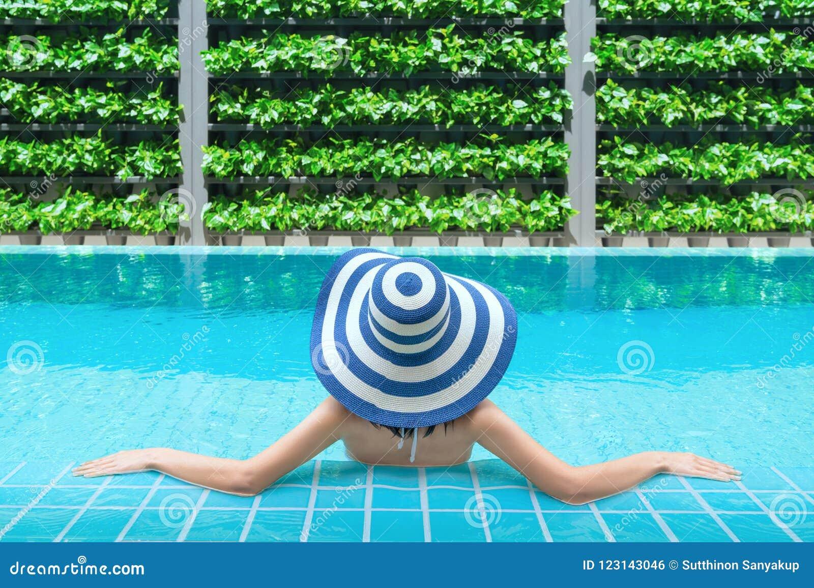 放松在游泳池的年轻亚裔妇女在温泉渡假胜地 放松的概念 妇女是松弛在游泳池边
