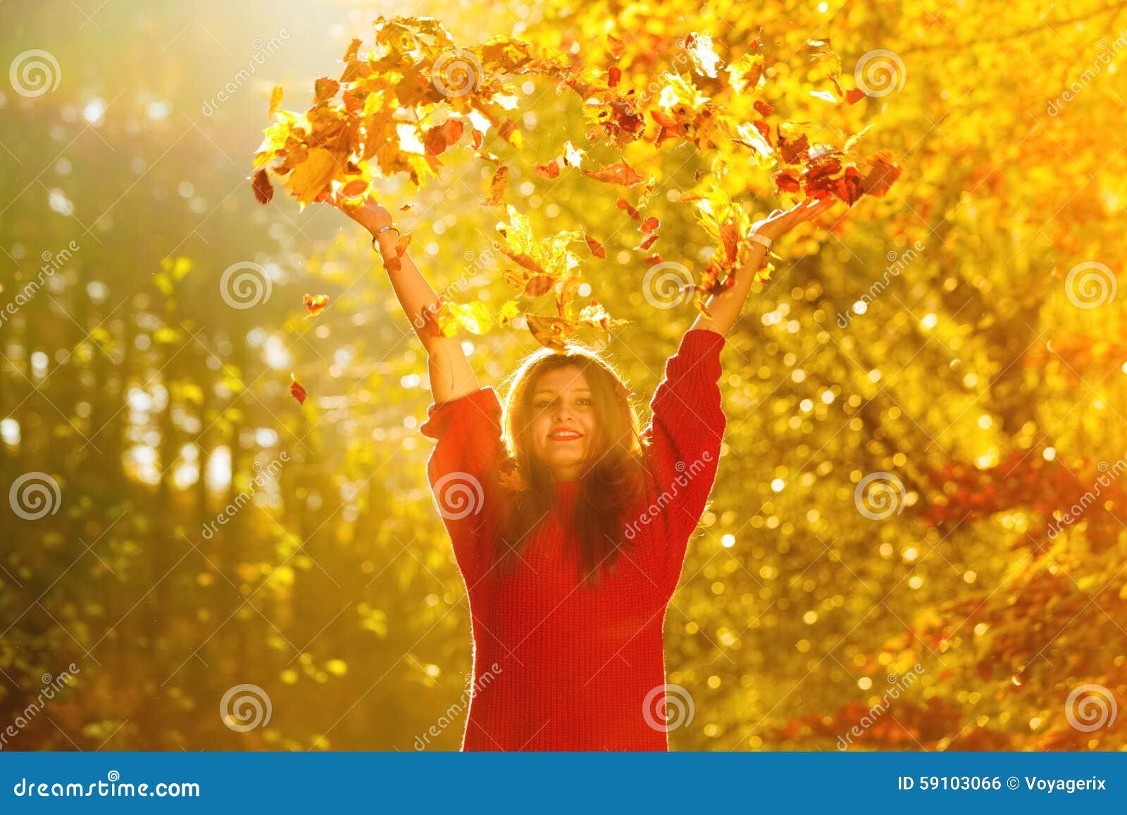 放松在秋天公园投掷的叶子的妇女悬而未决