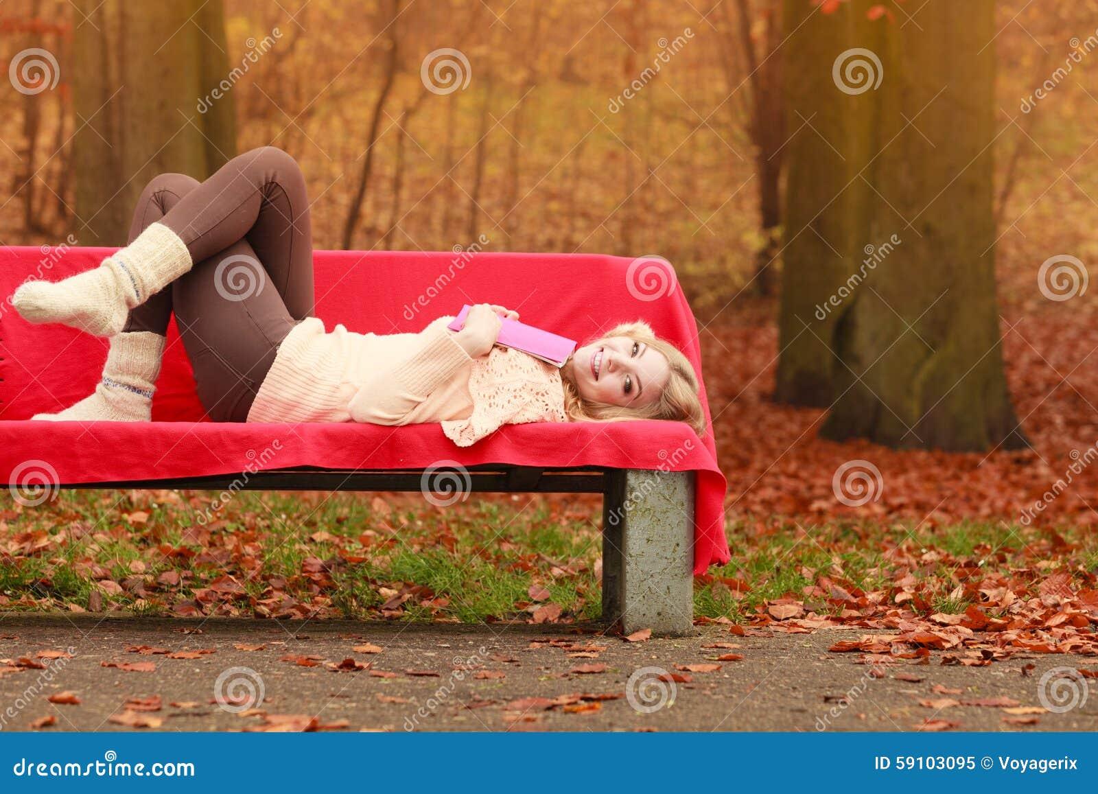 放松在秋天有书的秋天公园的妇女