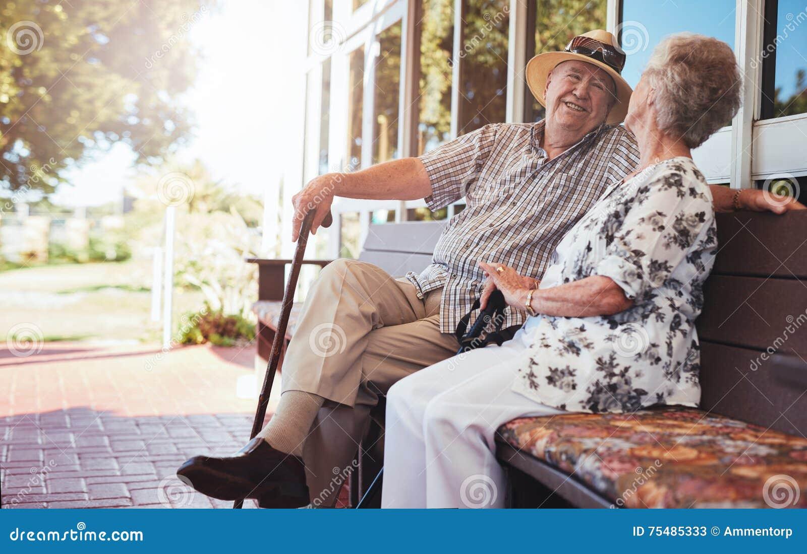 放松在长凳的愉快的资深夫妇他们的房子外