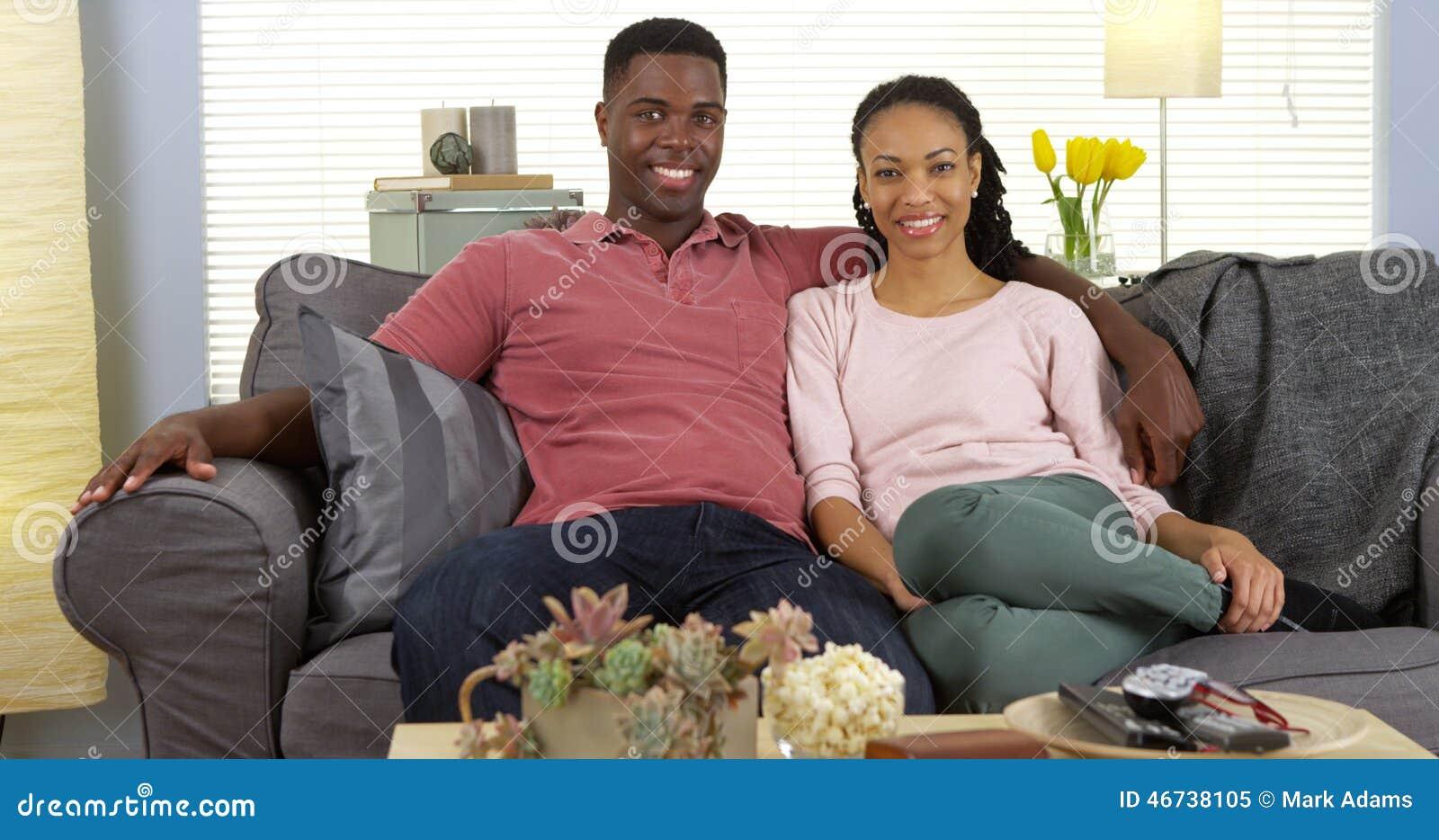放松在长沙发的愉快的年轻黑夫妇看照相机